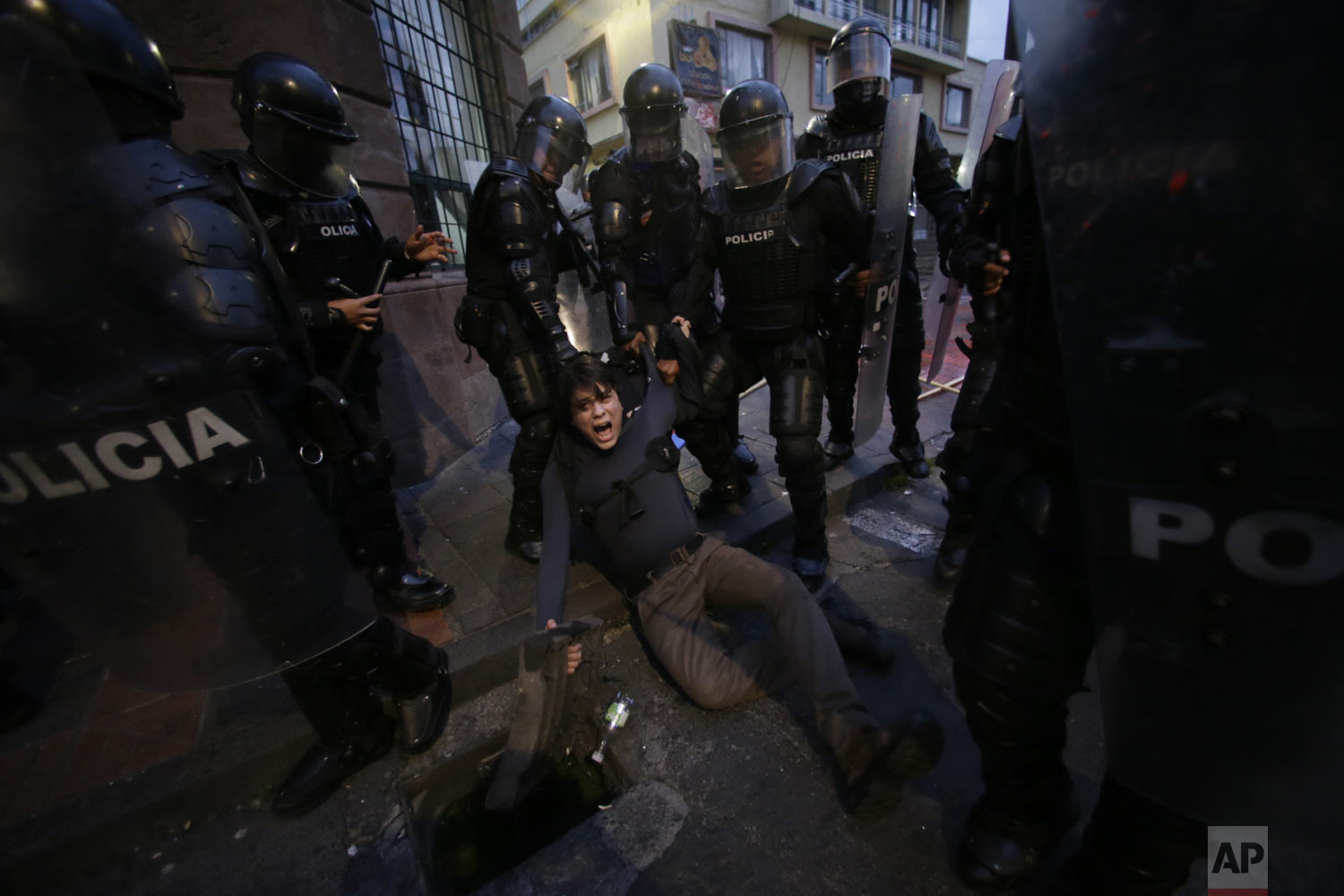 A man is detained by police blocking protesters from advancing closer to the presidential palace in Quito, Ecuador, Tuesday, April 16, 2019. Protesters were demonstrating against the policies of President Lenin Moreno's government, including the recent firing of state workers, the taking of an International Monetary Fund loan and the removal of Julian Assange's asylum status. (AP Photo/Dolores Ochoa)