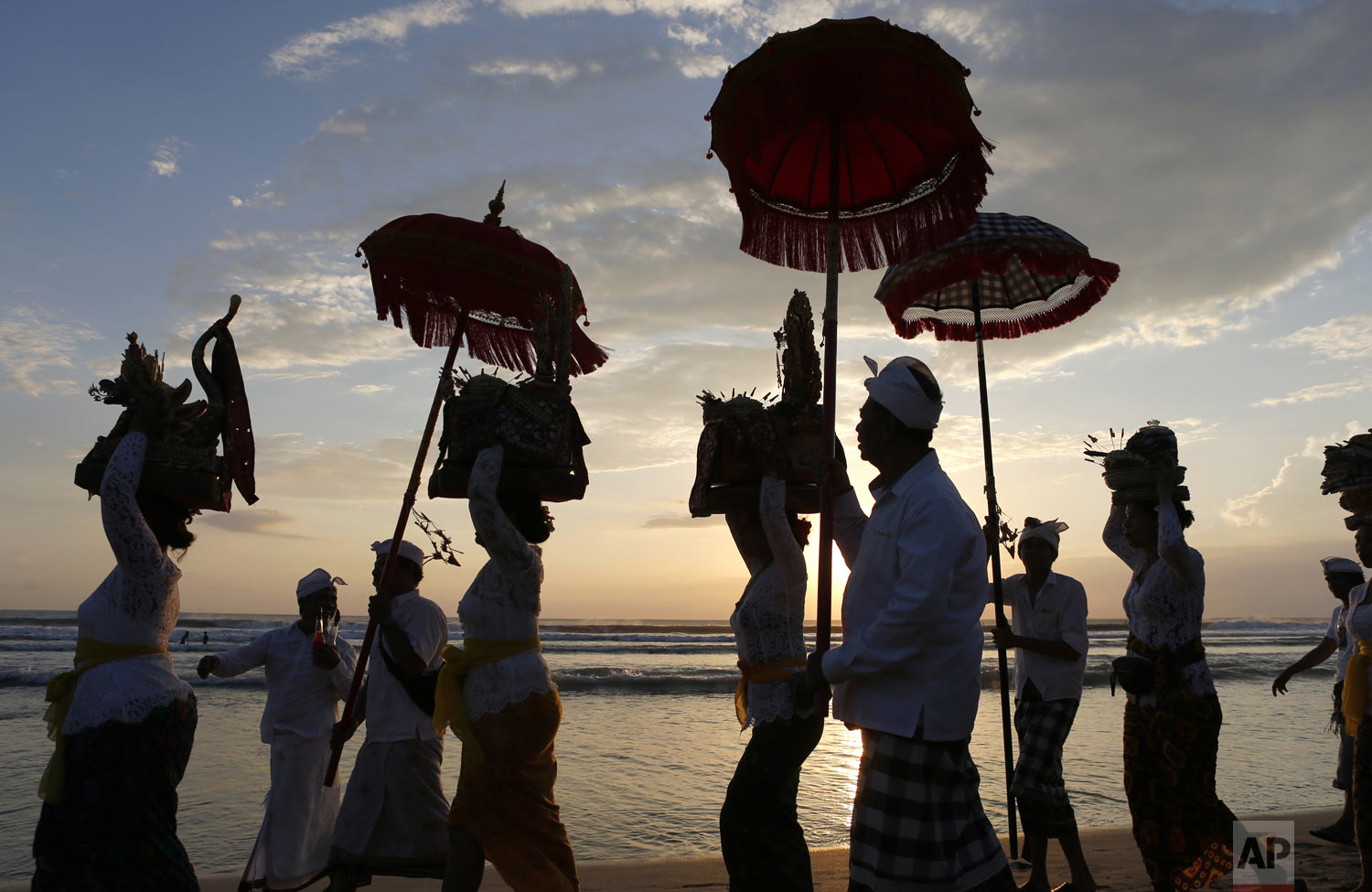Balinese Hindus walk on a beach carrying sacred ornaments during a full moon Hindu ritual in Bali, Indonesia, Friday, April 19, 2019. (AP Photo/Firdia Lisnawati)