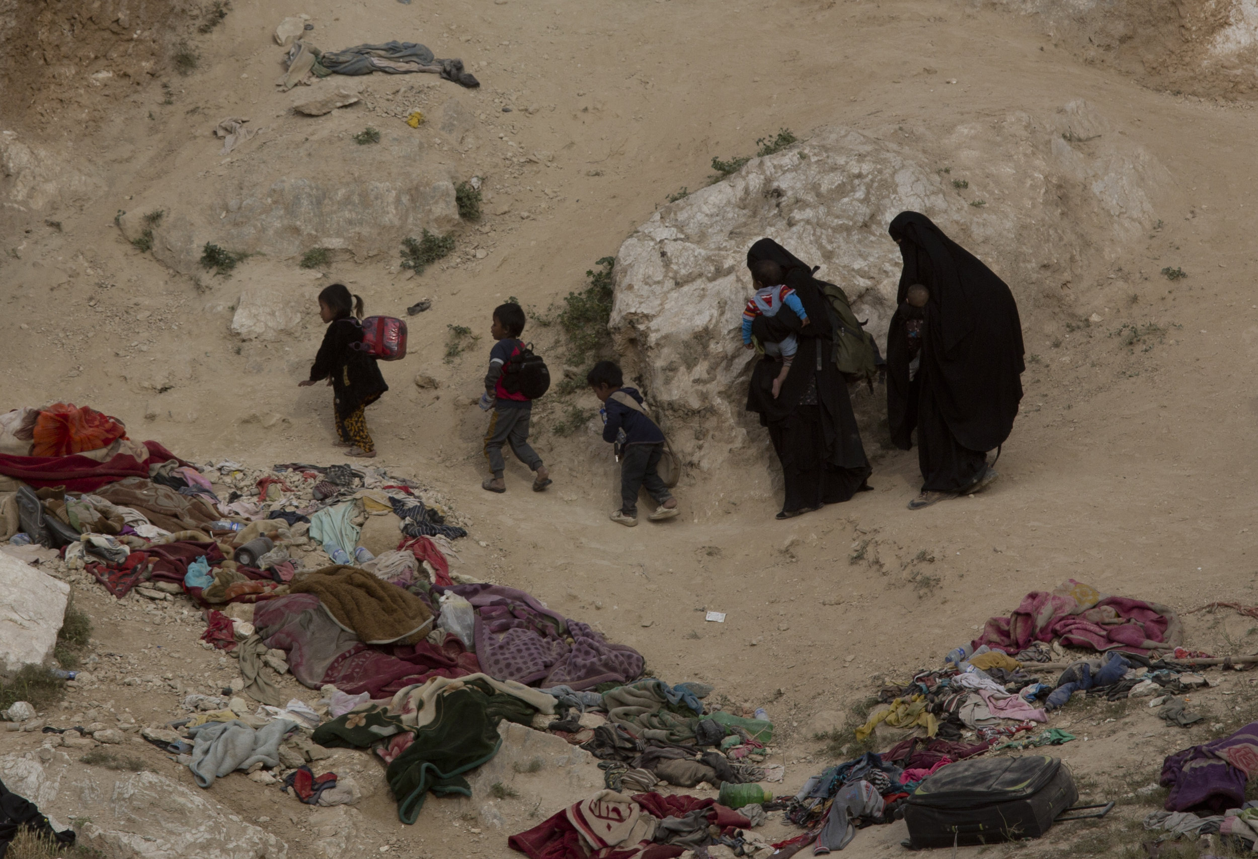 Women and their children who left the besieged Islamic State-held village of Baghouz, Syria, scramble over a rocky hillside to be checked by U.S-backed Syrian Democratic Forces on March 14, 2019. (AP Photo/Maya Alleruzzo)