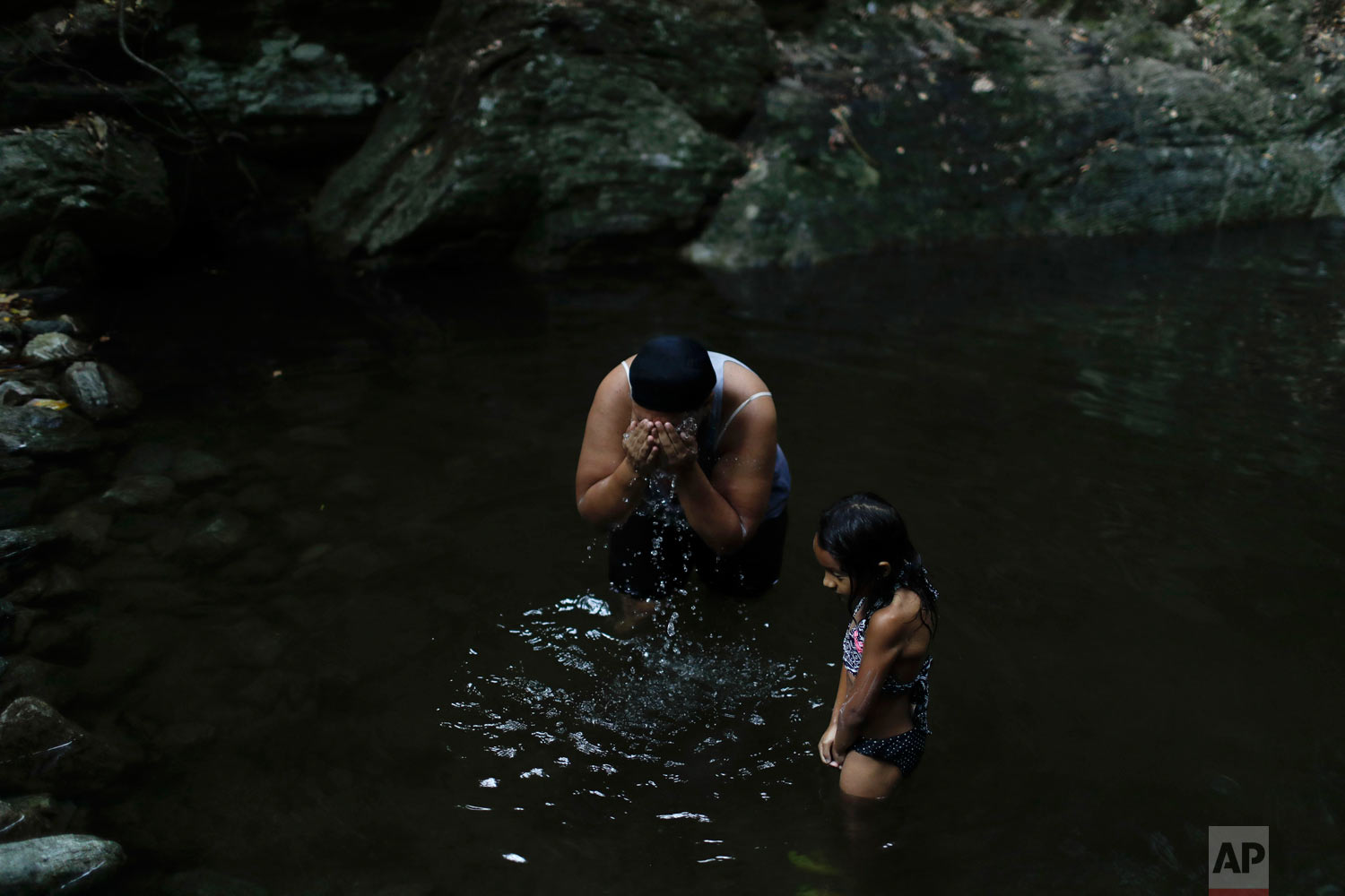 Liz Vargas and her niece Camila Vargas bathe in Avila National Park in Caracas, April 4, 2019. Vargas said she hasn't had running water at home for the previous 15 days, and this was the first time she'd come to bathe where she used to swim for fun. (AP Photo/Natacha Pisarenko)