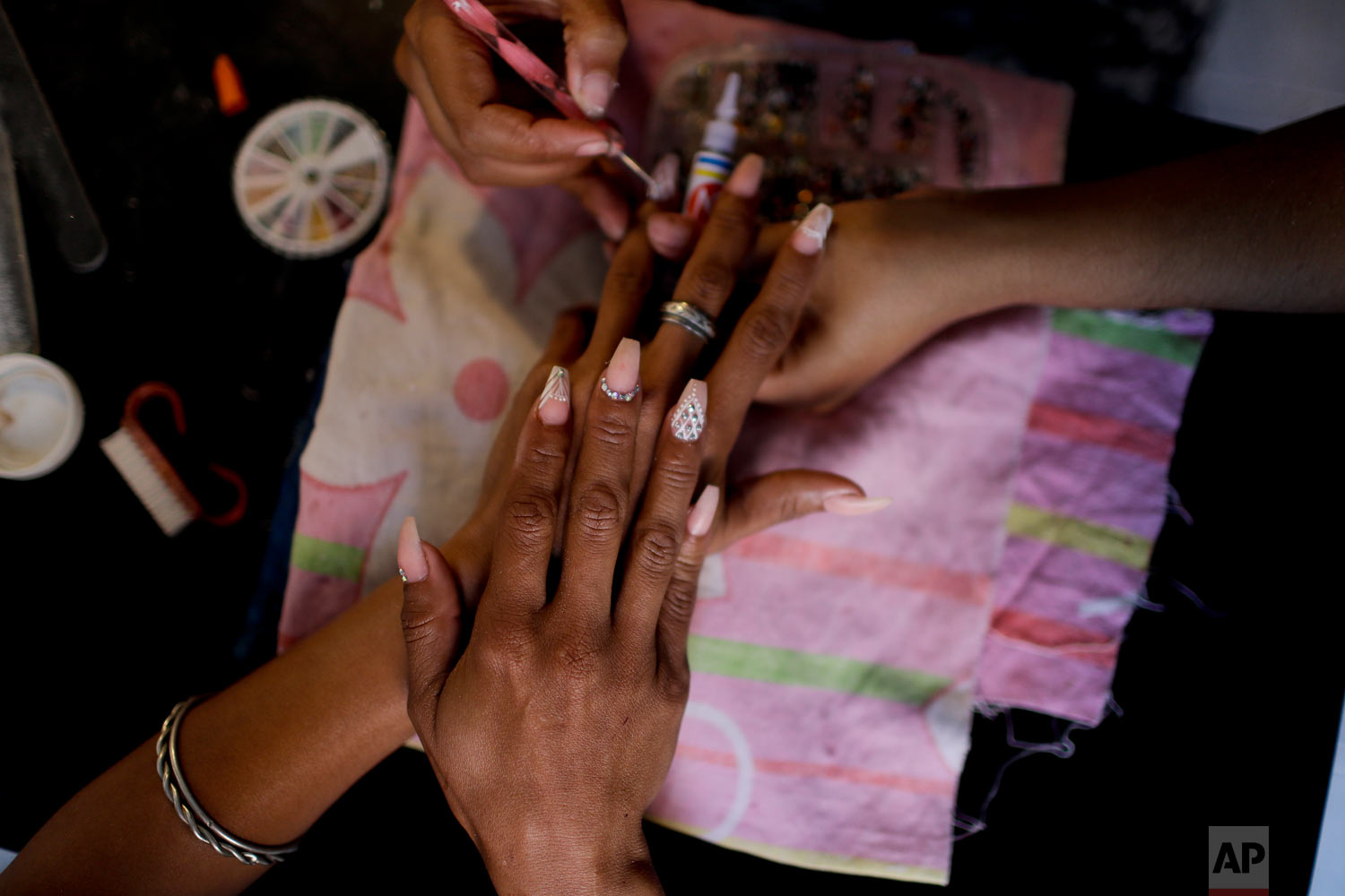 Yaris Colina gets her nails done at a beauty salon in Caracas, Venezuela, Friday, March 22, 2019.  (AP Photo/Natacha Pisarenko)