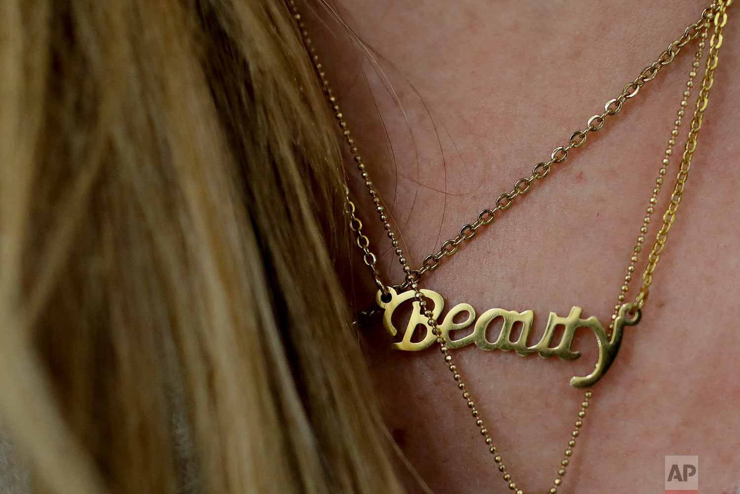 "Carolina Dejan wears a neckless featuring the word ""Beauty"" at a beauty salon where she is getting extensions using real hair from women who sold theirs in Caracas, Venezuela, Thursday, April 4, 2019. (AP Photo/Natacha Pisarenko)"
