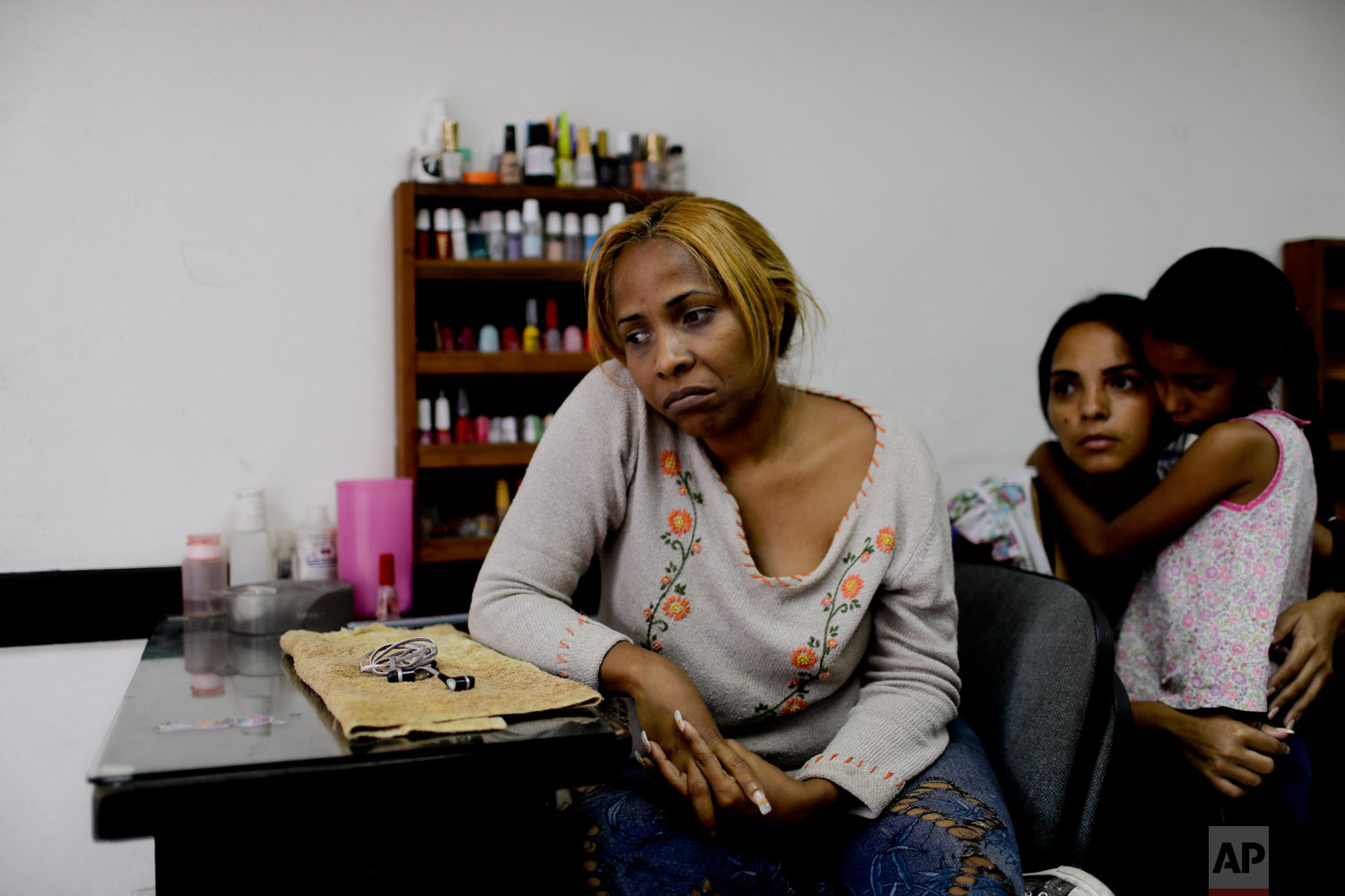 Manicurist Maria Trinidad Tobar waits for customers at a beauty salon in Caracas, Venezuela, Tuesday, March 19, 2019. (AP Photo/Natacha Pisarenko)