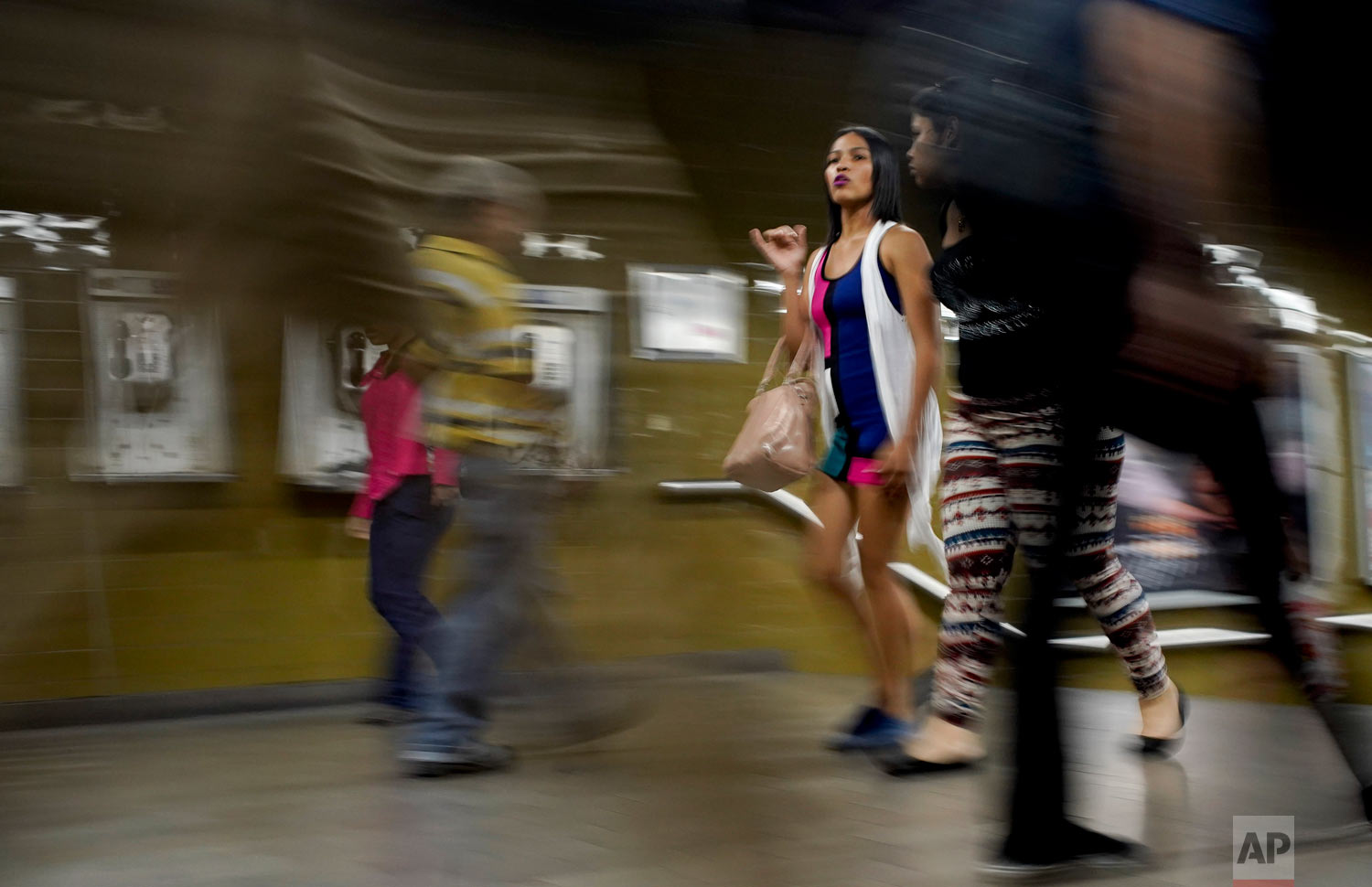 A woman wearing makeup and with her hair straightened walks through the subway in Caracas, Venezuela, Friday, March 22, 2019. (AP Photo/Natacha Pisarenko)