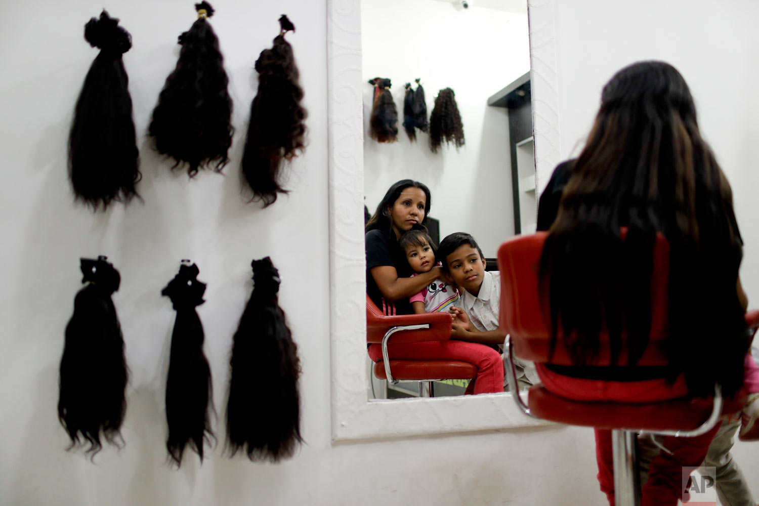 Nelly Navarro sits with her kids Nerianny and Luis in a beauty salon where she came to consult how much money she could get for her hair, in Caracas, Venezuela, Tuesday, April 2, 2019. Navarro said she needs the $100 to travel to Colombia where she's planning to move. (AP Photo/Natacha Pisarenko)