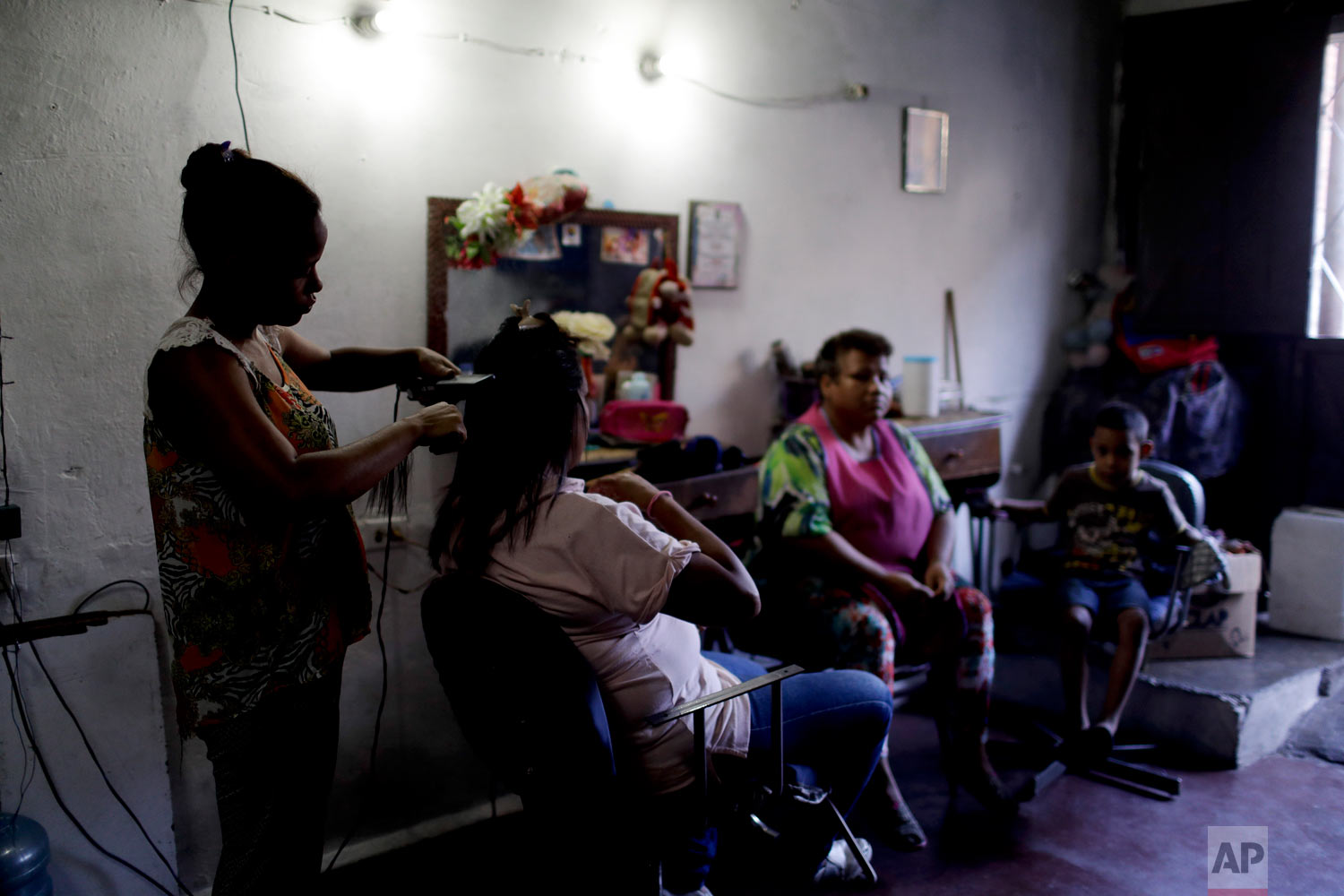 Hair dresser Rosevel Velazquez attends a customer at her beauty salon, which she runs out of her home in Caracas, Venezuela, Wednesday, March 20, 2019.  (AP Photo/Natacha Pisarenko)