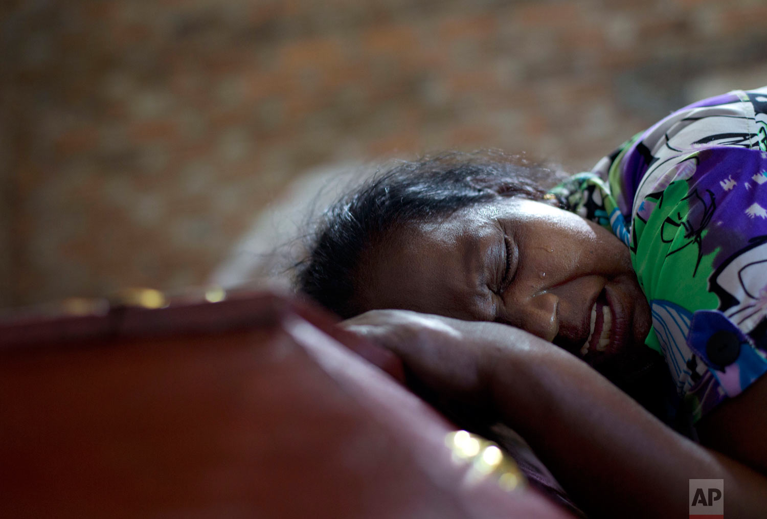 Lalitha weeps on the coffin with the remains of 12-year old niece, Sneha Savindi, who was a victim of Easter Sunday bombing at St. Sebastian Church in Negombo, Sri Lanka, April 22, 2019. (AP Photo/Gemunu Amarasinghe)