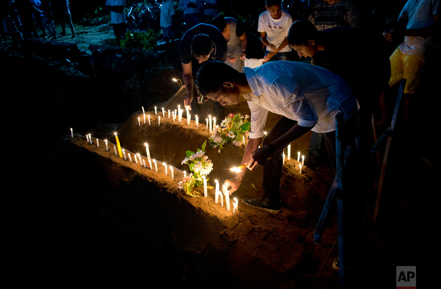 Relatives light candles after burial of three victims of the same family, who died at Easter Sunday bomb blast at St. Sebastian Church in Negombo, Sri Lanka, April 22, 2019. (AP Photo/Gemunu Amarasinghe)