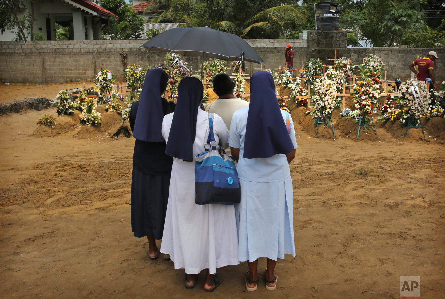 Catholic nuns stand with a relative of a victim of Easter Sunday's bomb blast at St. Sebastian Church at a mass burial site in Negombo, Sri Lanka, April 25, 2019. (AP Photo/Manish Swarup)