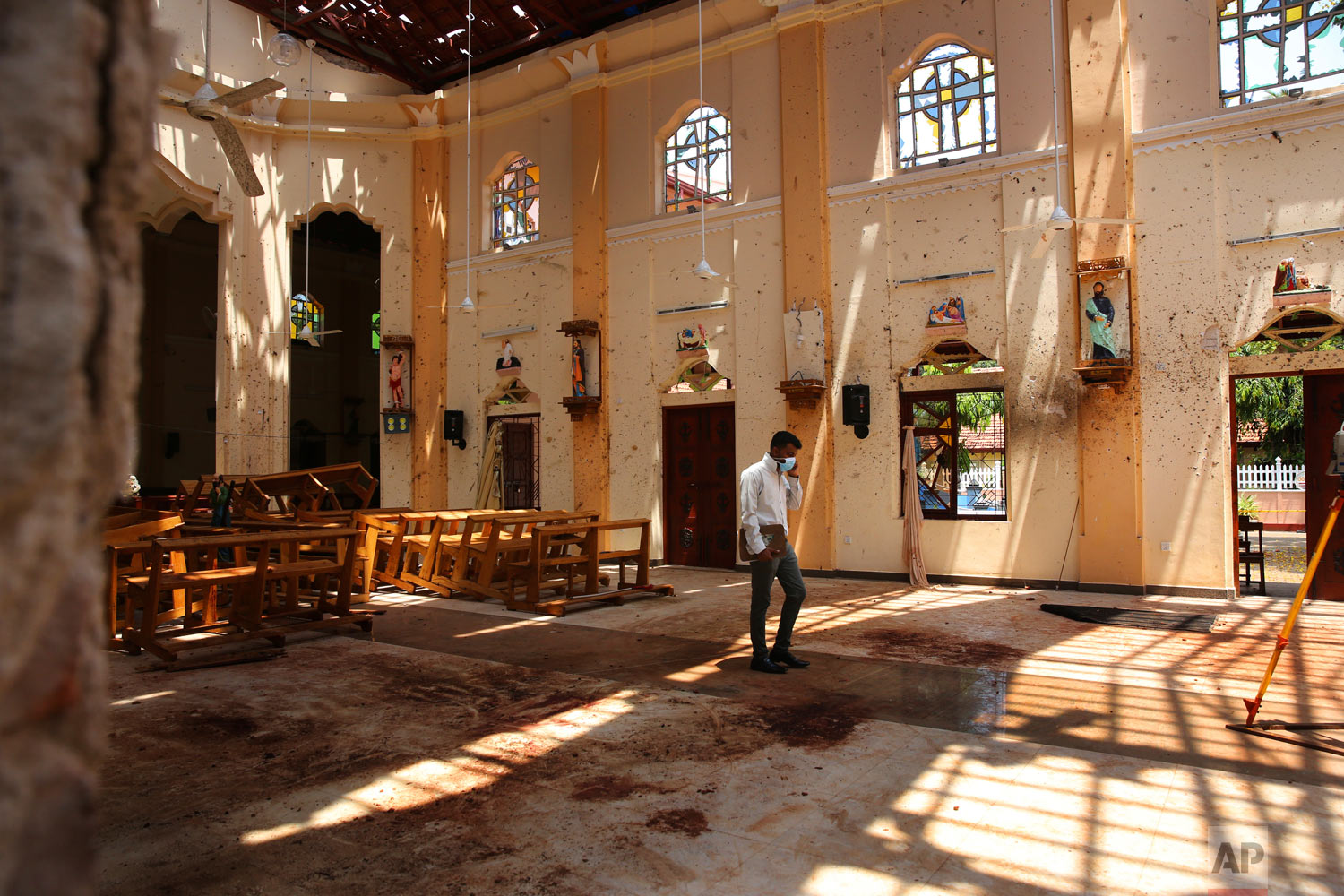 A surveyor walks inside the damaged St. Sebastian's Church where a suicide bomber blew himself up on Sunday Easter in Negombo, north of Colombo, Sri Lanka, April 25, 2019. (AP Photo/Manish Swarup)