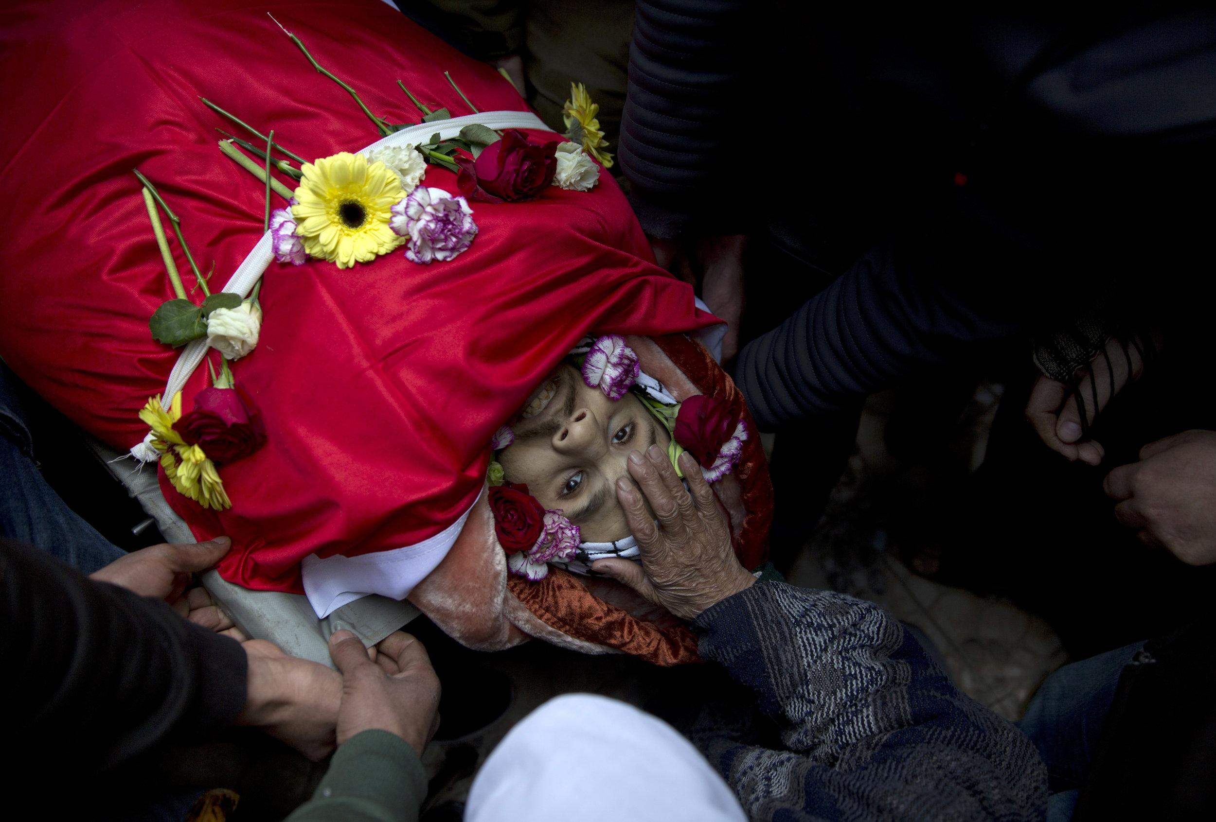 Mourners take a farewell look at the body of Mohammad Edwan, 23, who was shot and killed by Israeli troops, in the West Bank Refugee camp of Qalandia, near Ramallah, Tuesday, April 2, 2019. (AP Photo/Nasser Nasser)
