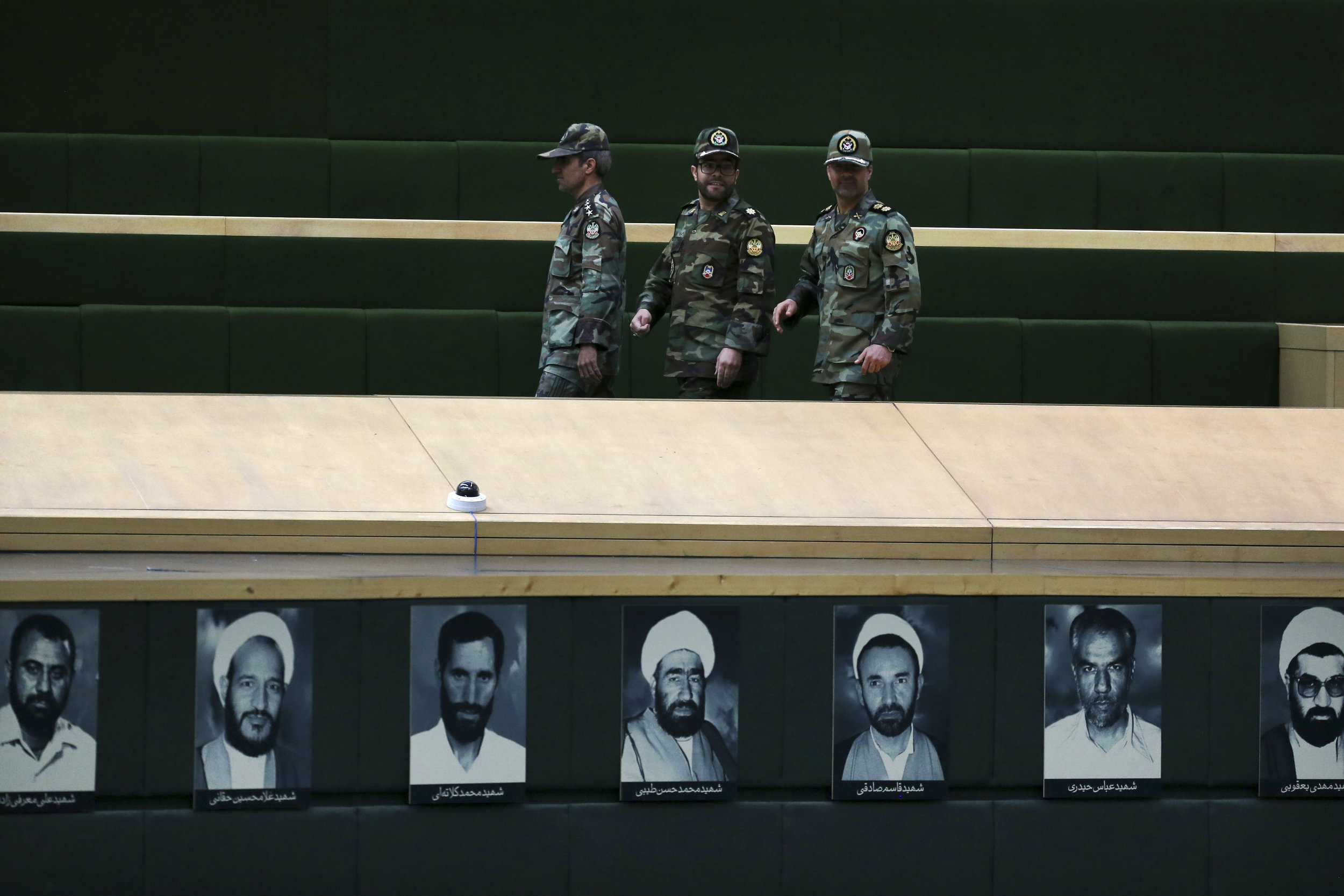 Iranian troops walk past pictures late lawmakers on a tour of parliament on the occasion of Army Day on Thursday, in Tehran, Iran, Tuesday, April 16, 2019. (AP Photo/Vahid Salemi)