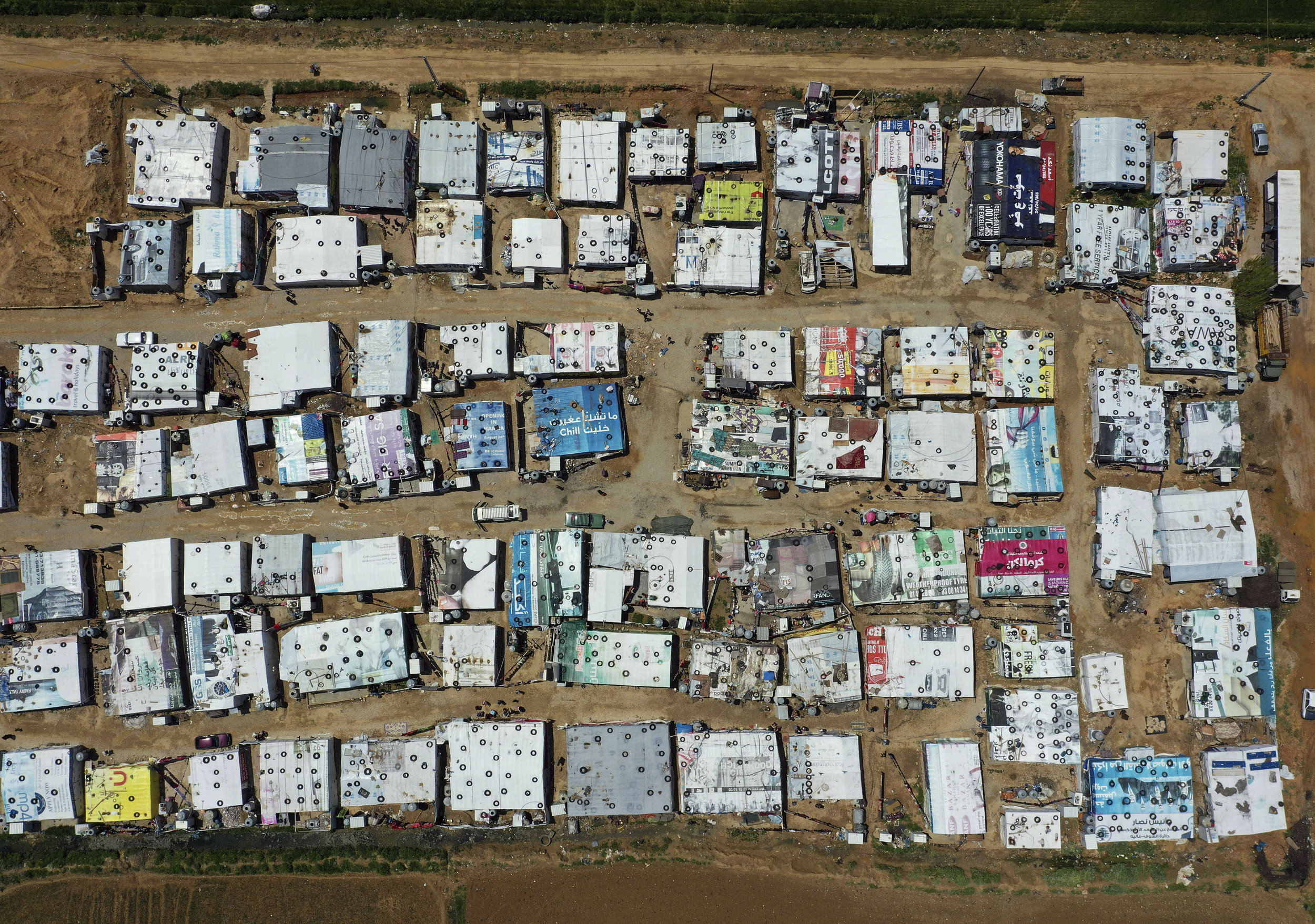 An aerial view shows an informal Syrian refugee camp, in the Bekaa valley town of Saadnayel, east Lebanon, Tuesday, April 23, 2019. (AP Photo/Hussein Malla)