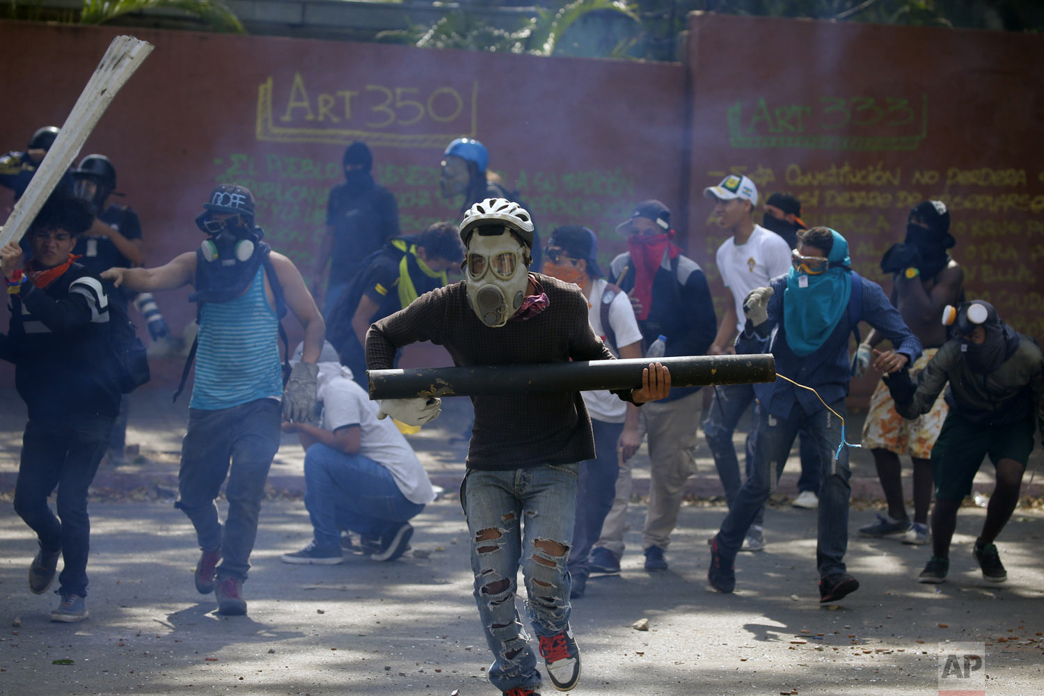 Anti-government protesters, one carrying a homemade mortar, take cover as security forces fire tear gas to disperse demonstrators in Caracas, Venezuela, Wednesday, May 1, 2019. Opposition leader Juan Guaidó called for Venezuelans to fill streets around the country Wednesday to demand President Nicolás Maduro's ouster. Maduro is also calling for his supporters to rally. (AP Photo/Fernando Llano)