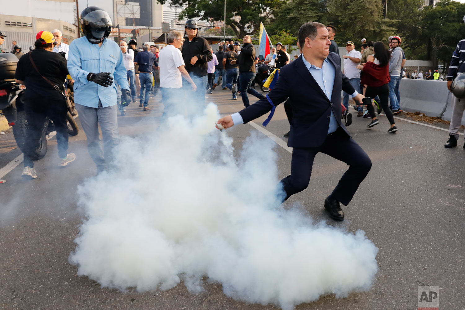 An opponent to Venezuela's President Nicolas Maduro returns a tear gas canister to soldiers who launched it at a small group of civilians and rebel troops gathered outside La Carlota air base in Caracas, Venezuela, April 30, 2019. (AP Photo/Ariana Cubillos)