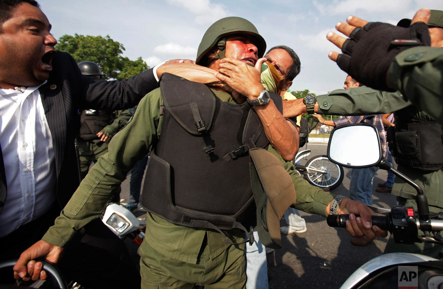 Opponents to Venezuela's President Nicolas Maduro, behind and left, scuffle with a National Guard who is loyal to President Nicolas Maduro during clashes with rebel soldiers attempting a military uprising outside La Carlota military airbase in Caracas, Venezuela, April 30, 2019.  (AP Photo/Boris Vergara)