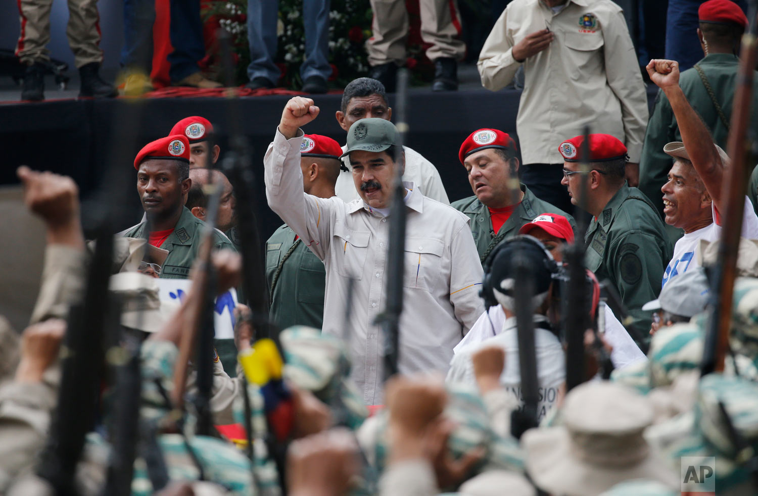 Venezuela's President Nicolas Maduro cheers the Bolivarian Militia during their 10th anniversary celebration in Caracas, Venezuela, Saturday, April 13, 2019. Officially known as the Venezuelan National Bolivarian Militia, it is a branch of the National Armed Forces of Venezuela created by the late President Hugo Chavez and today it is made up of over 2 million men and women. (AP Photo/Ariana Cubillos)