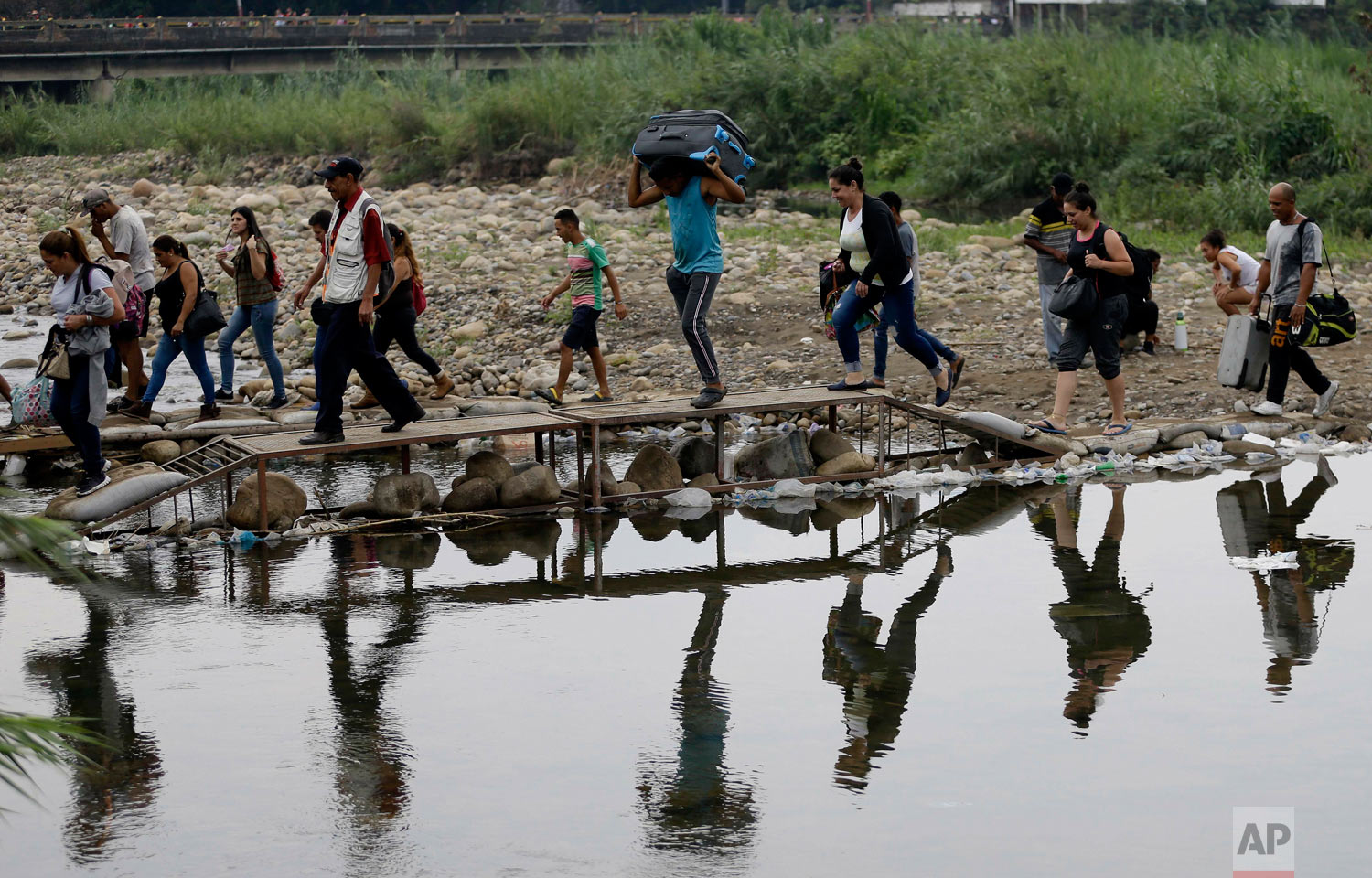 Venezuelans cross illegally into Colombia near the Simon Bolivar International Bridge, behind, top left, which is partially closed by Venezuelan authorities who are only permitting students, seniors and the sick to cross, seen from La Parada near Cucuta, Colombia, April 14, 2019. U.S. (AP Photo/Fernando Vergara)