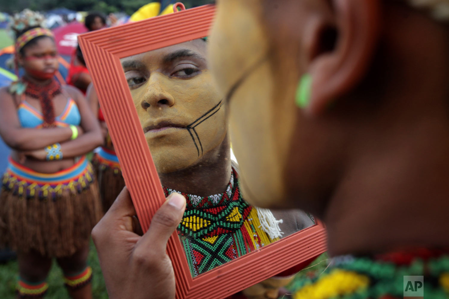 An indigenous man applies body paint during an annual campout protest for indigenous rights known as the Free Land Encampment in Brasilia, Brazil, April 24, 2019. (AP Photo/Eraldo Peres)