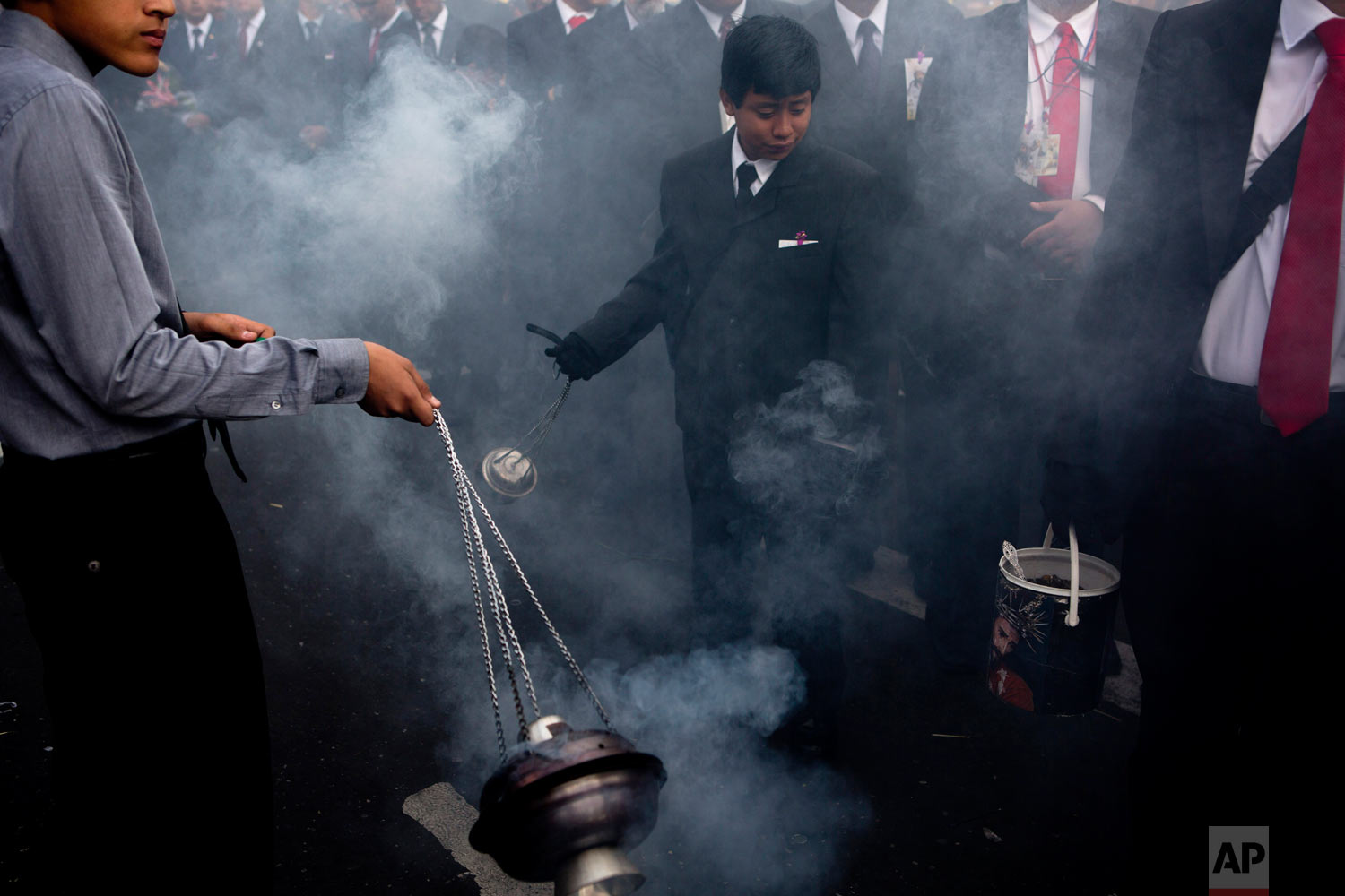 """Boys swing burners with incense purifying the path of the """"La Reseña,"""" procession known as """"La Reseña"""" in downtown Guatemala City, April 16, 2019. (AP Photo/Moises Castillo)"""