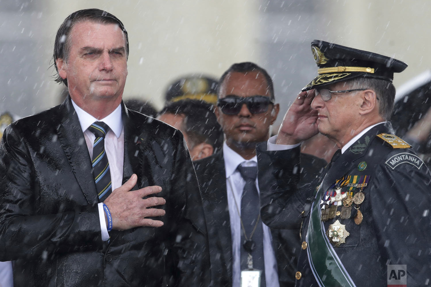 Brazil's President Jair Bolsonaro puts his hand over his heart as Army Commander Edson Leal Pujol salutes during the playing of the national anthem during a ceremony marking Army Day, in Brasilia, Brazil, April 17, 2019. (AP Photo/Eraldo Peres)