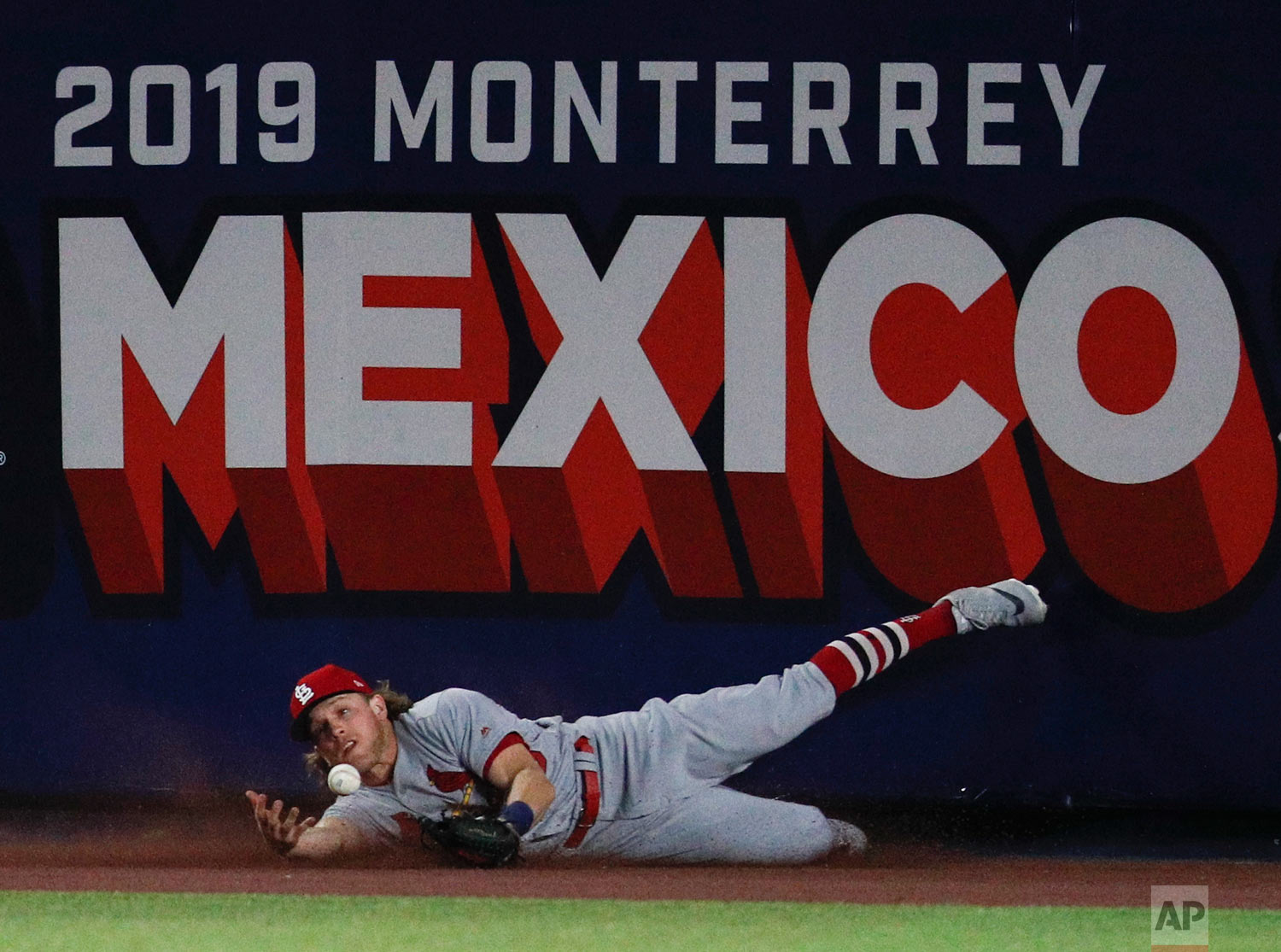 St. Louis Cardinals' Harrison Bader can't make the catch on a triple by Cincinnati Reds' Phillip Ervin during the eighth inning of a baseball game in Monterrey, Mexico, April 13, 2019. The Reds defeated the Cardinals 5-2. (AP Photo/Rebecca Blackwell)