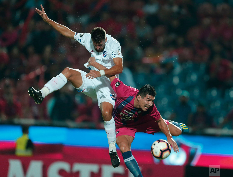 Marcos Caceres, right, of Paraguay's Cerro Porteno fights for the ball with Joaquin Azura of Uruguay's Nacional during a Copa Libertadores soccer game, in Asuncion, Paraguay, April 2, 2019. (AP Photo/Jorge Saenz)