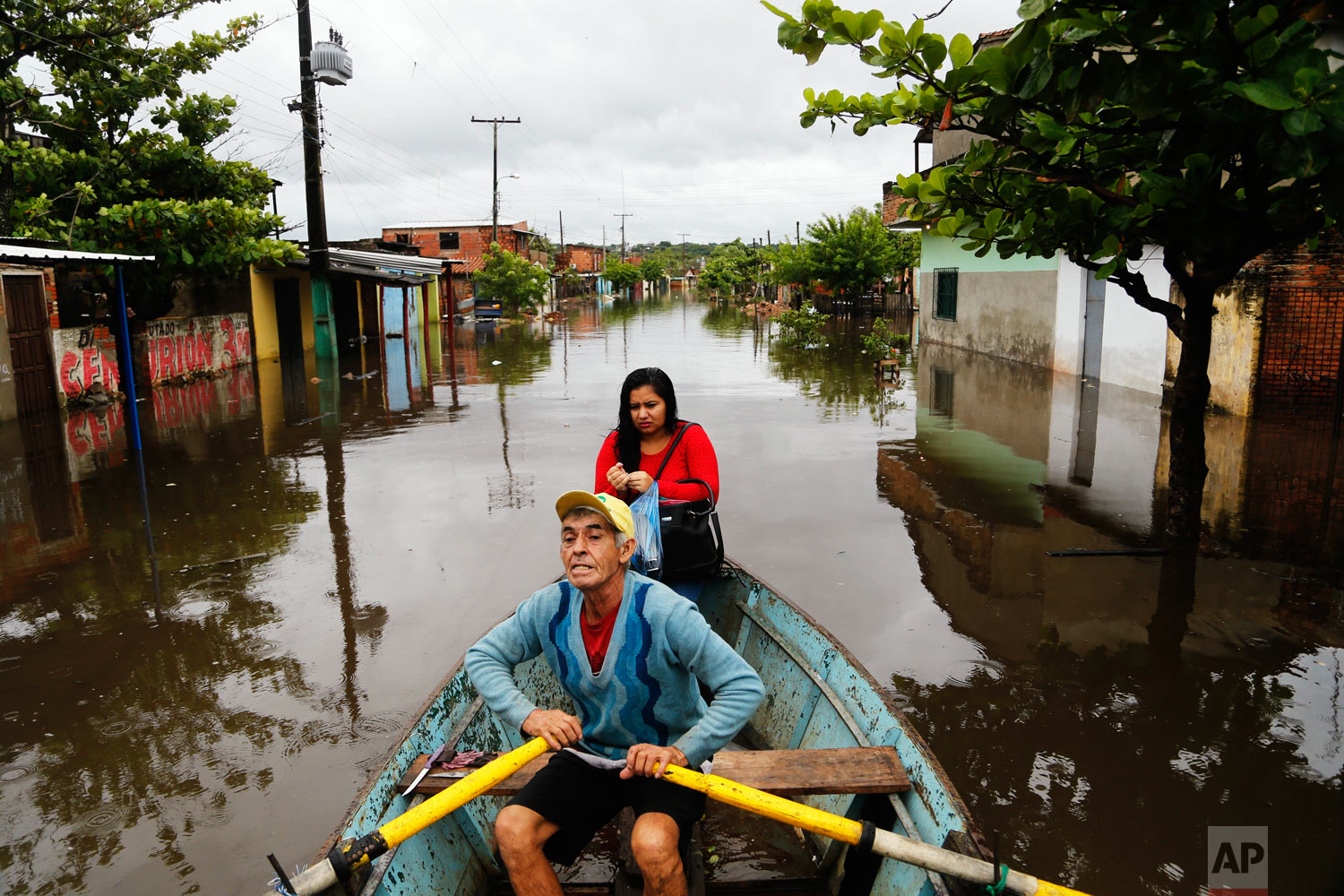 With his daughter as passenger, Ramon Gomez, 65, rows a boat through a flooded street in the Santa Rosa de Lima neighborhood, in Asuncion, Paraguay, April 5, 2019. (AP Photo/Jorge Saenz)
