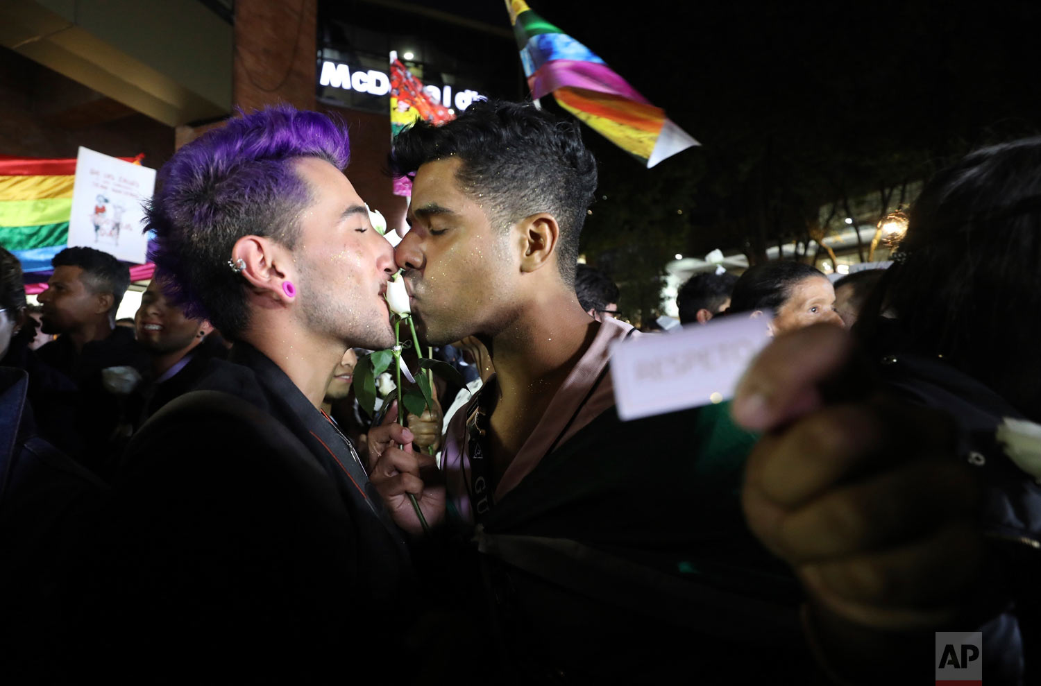 """A same sex couple kiss a rose during a """"Kiss-a-thon,"""" as a form of protest for LGBT rights and against discrimination in Bogota, Colombia, April 17, 2019. (AP Photo/Fernando Vergara)"""