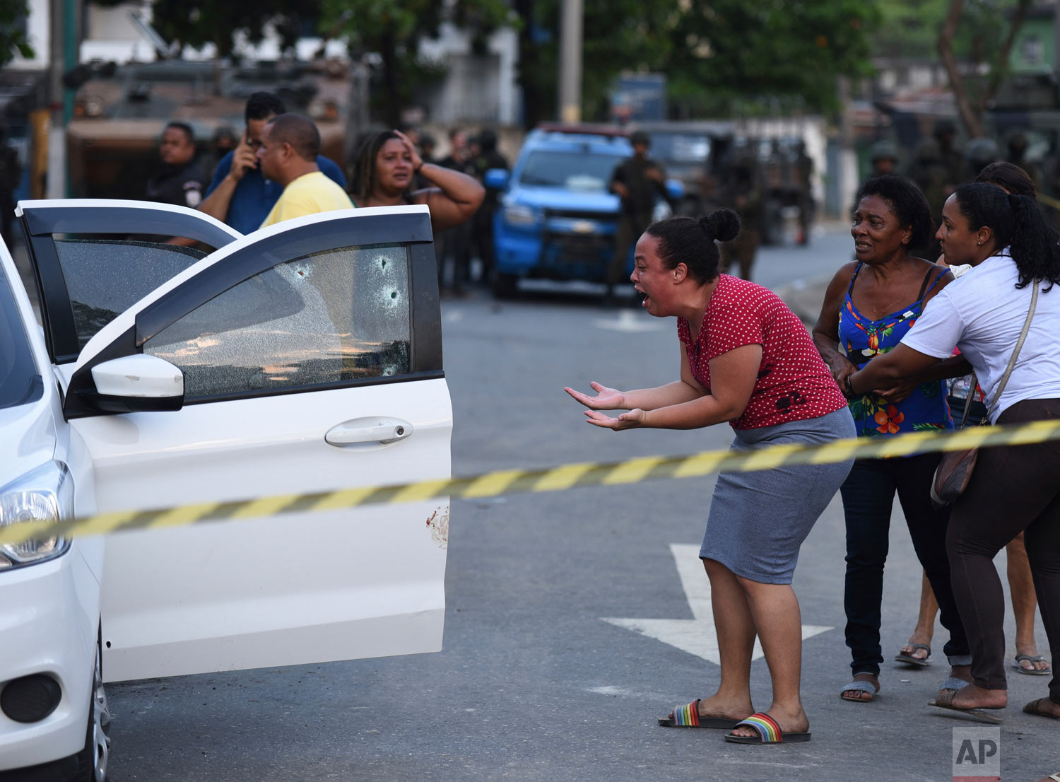 A woman cries out in agony as she looks at the body of Evaldo dos Santos Rosa slumped inside his car in the Guadalupe neighborhood of Rio de Janeiro, Brazil, April 7, 2019. Authorities say soldiers mistook Evaldo dos Santos Rosa's for that of criminals and was hit by 80 shots fired by members of the armed forces, killing him and wounding his wife's stepfather. (AP Photos/Fabio Teixeira)