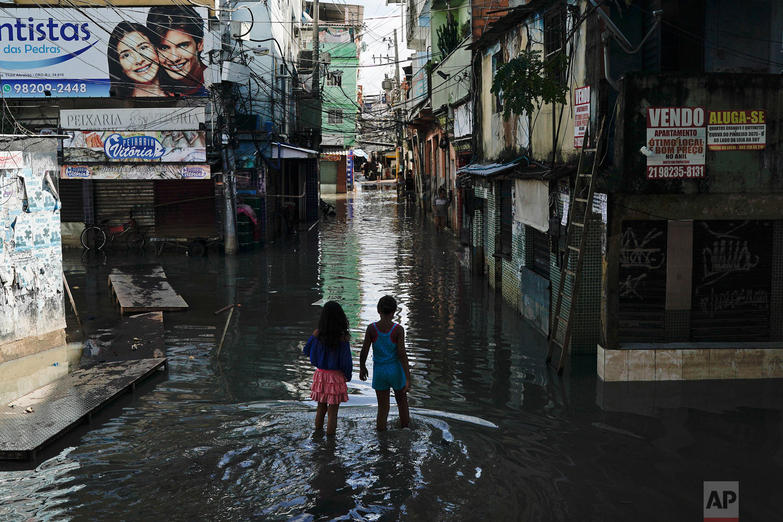 Children walk through a flooded street in Rio de Janeiro, Brazil, April 10, 2019. (AP Photo/Leo Correa)
