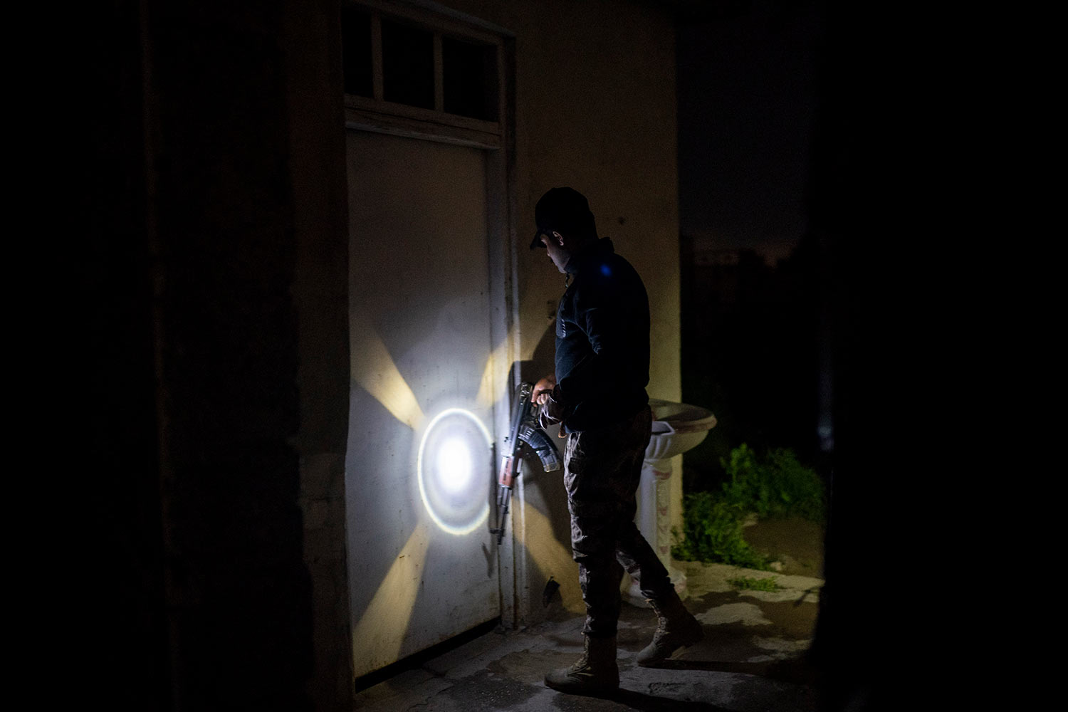In this April 2, 2019 photo, an Iraqi army 20th division soldier uses his AK-47 riffle to knock on a door during a nighttime raid near Badoush, Iraq. (AP Photo/Felipe Dana)