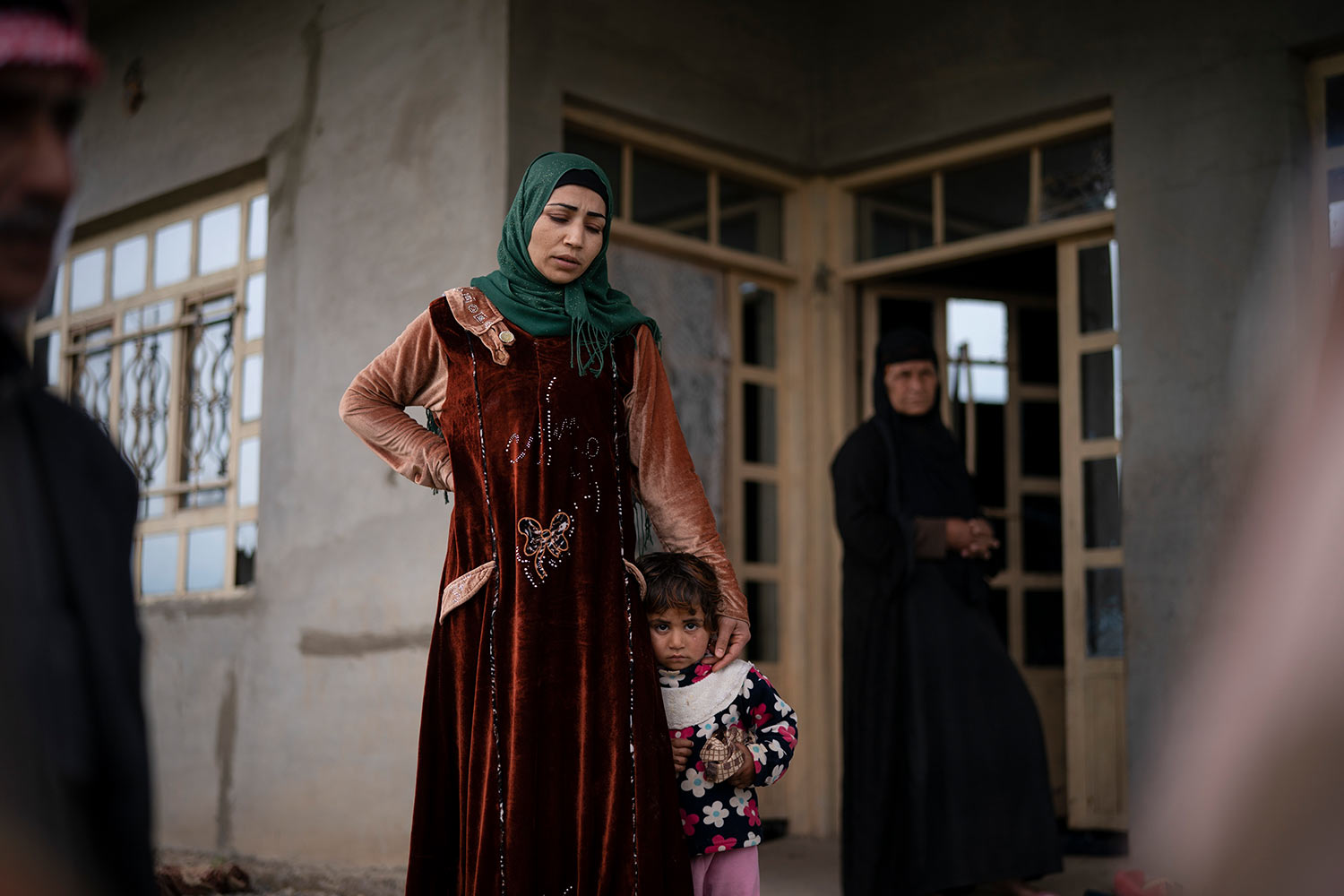 In this April 5, 2019 photo, a woman holds her daughter as she answer questions by Iraqi army 20th division soldiers during a raid in Badoush, Iraq. (AP Photo/Felipe Dana)