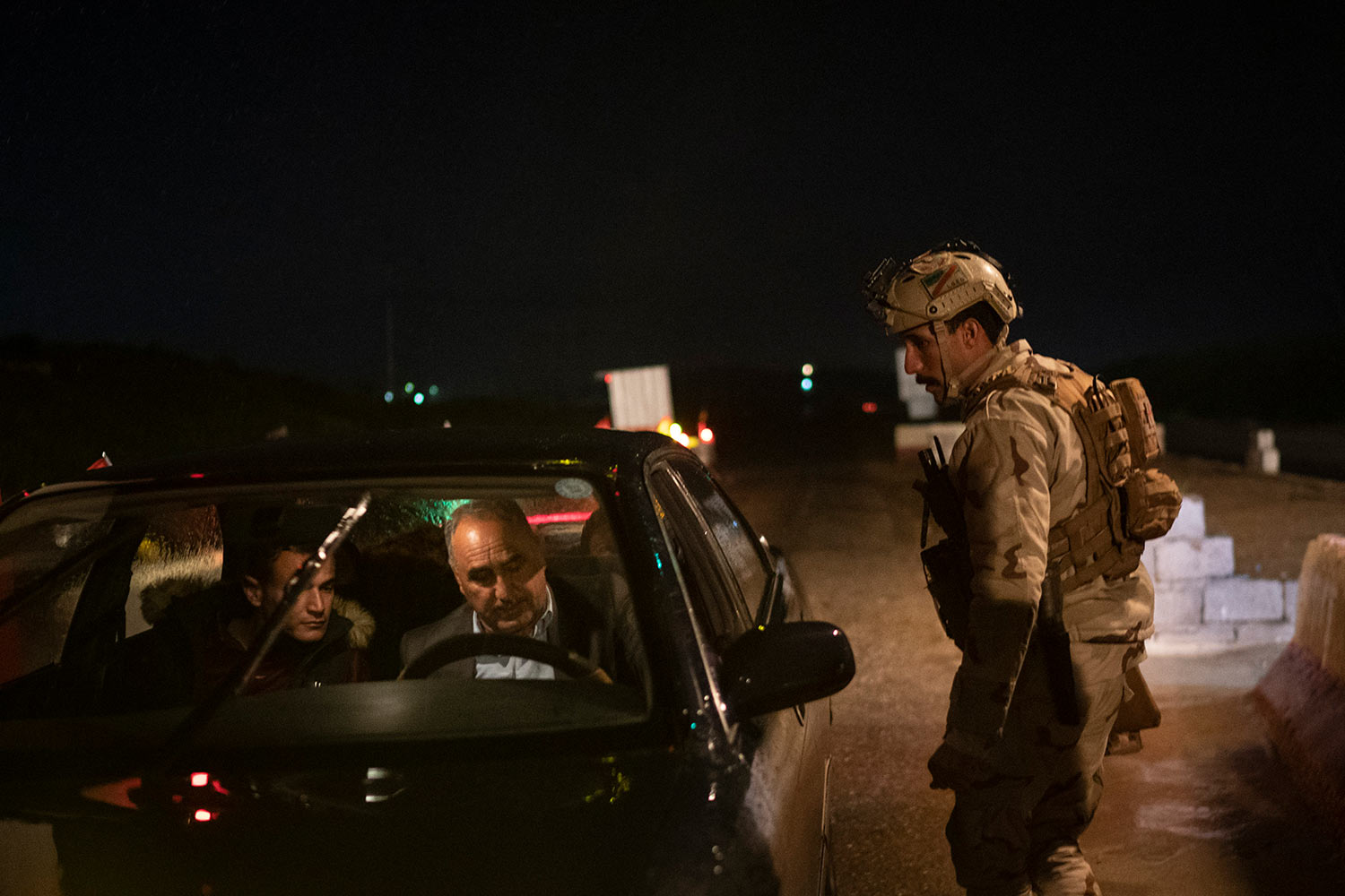 In this April 2, 2019 photo, an Iraqi army 20th division soldier asks for documents at a checkpoint near Badoush, Iraq. (AP Photo/Felipe Dana)