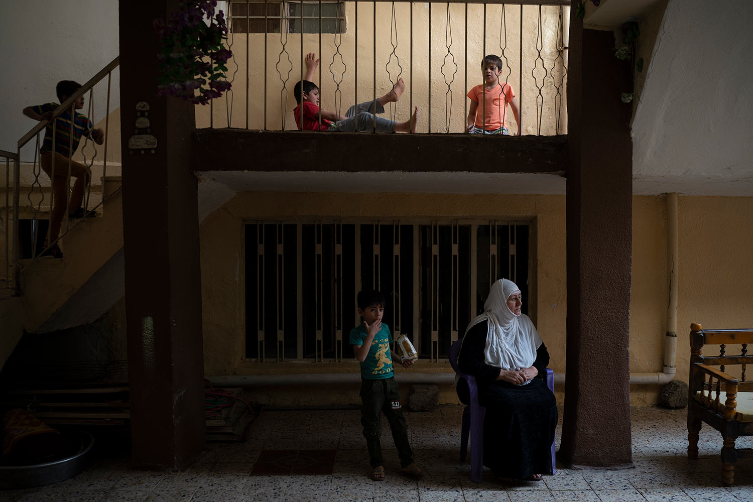 In this April 14, 2019 photo, Yusra Dhanoun sits as her grand children play in her house in Mosul, Iraq. Dhanoun three sons were killed by Islamic State militants in a chilling attack last January. (AP Photo/Felipe Dana)