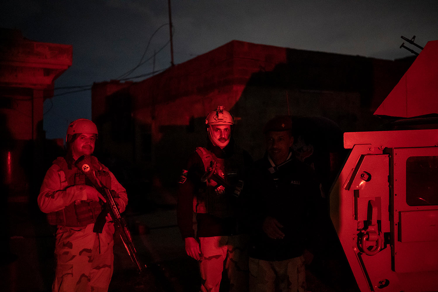 In this April 2, 2019 photo, Iraqi army 20th division soldiers stands next to a Humvee during a nighttime raid near Badoush, Iraq. (AP Photo/Felipe Dana)