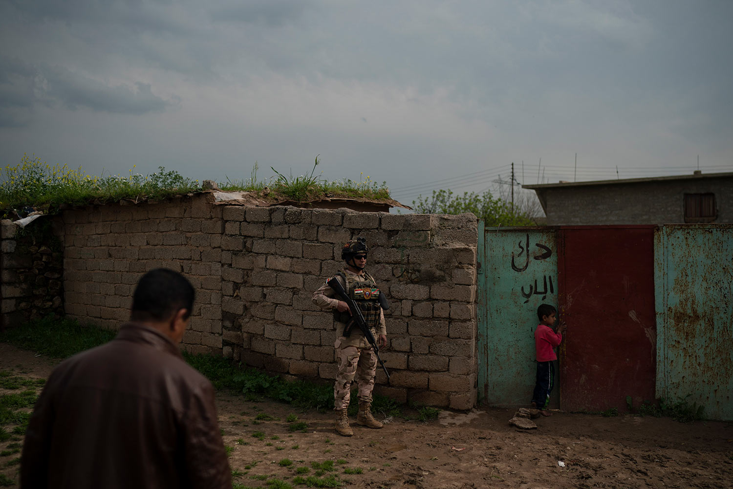 In this April 3, 2019 photo, an Iraqi army 20th division soldier waits outside a house during a patrol in Badoush area, Iraq. (AP Photo/Felipe Dana)