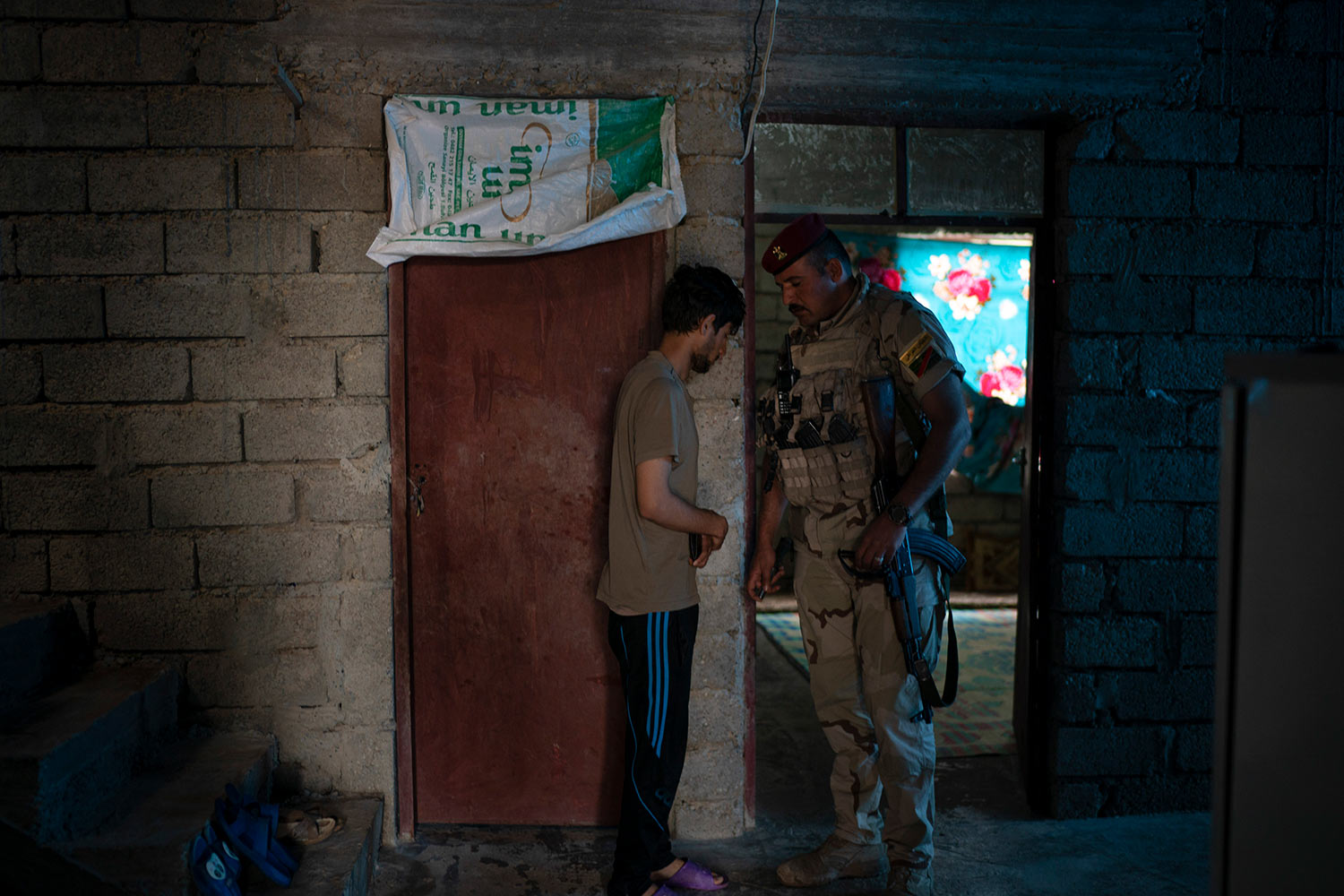 In this April 5, 2019 photo, an Iraqi army 20th division soldier talks to a suspect as they search his house during a raid in Badoush, Iraq. He taken into custody and then released after he was able to prove his whereabouts during IS rule. (AP Photo/Felipe Dana)