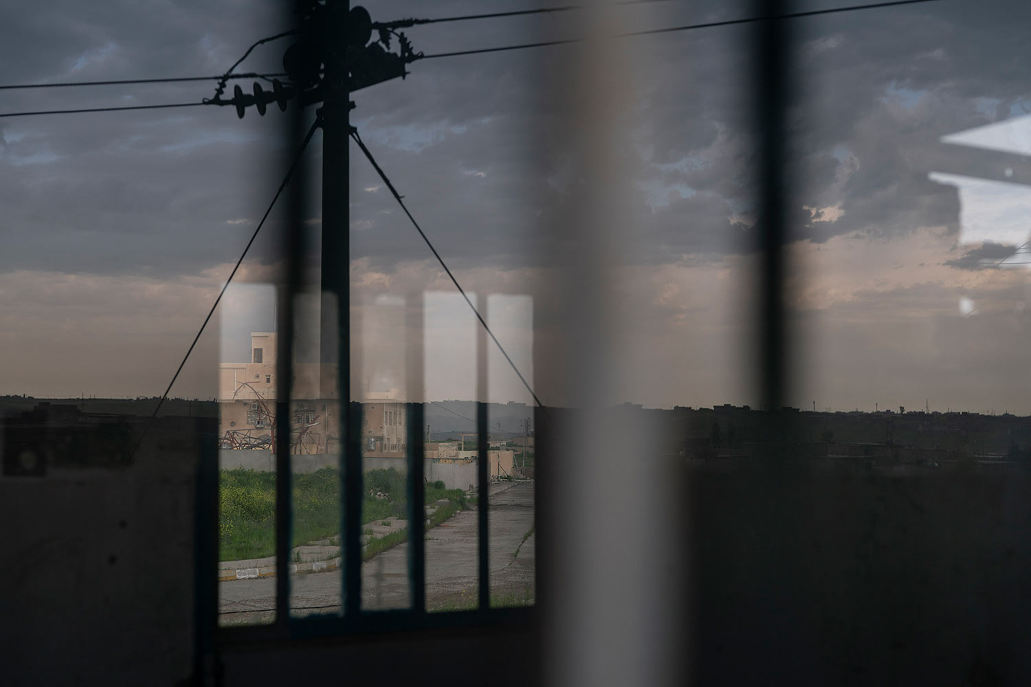 In this April 10, 2019 photo, houses are reflected on the window of an Iraqi army base in Badoush, Iraq. (AP Photo/Felipe Dana)