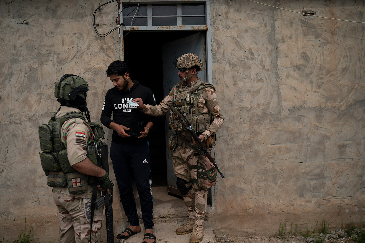 In this April 5, 2019 photo, Iraqi army 20th division soldiers check the ID of a man during a raid in Badoush, Iraq. (AP Photo/Felipe Dana)