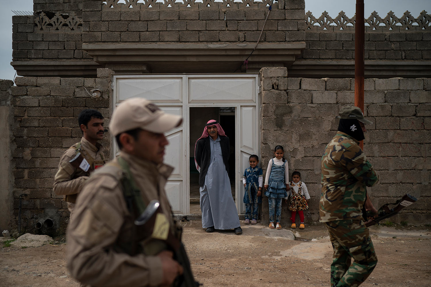 In this April 5, 2019 photo, residents watch as local militia and Iraqi army soldiers walk past their home during a raid in Badoush, Iraq. (AP Photo/Felipe Dana)