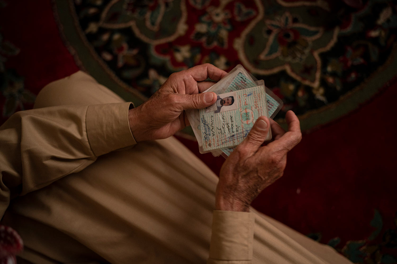 In this April 14, 2019 photo, Hussein Abd holds the ID's of his three dead sons as he sits in his house during an interview in Mosul, Iraq. They were killed in their home in Badoush by Islamic State militants in a chilling attack last January. (AP Photo/Felipe Dana)
