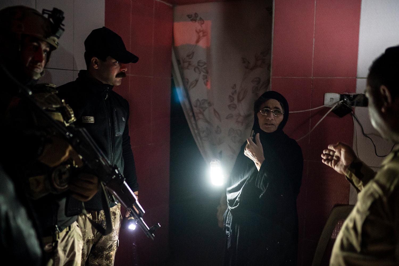 In this April 2, 2019 photo, Iraqi army 20th division soldiers talk to a woman during a nighttime raid near Badoush, Iraq. (AP Photo/Felipe Dana)