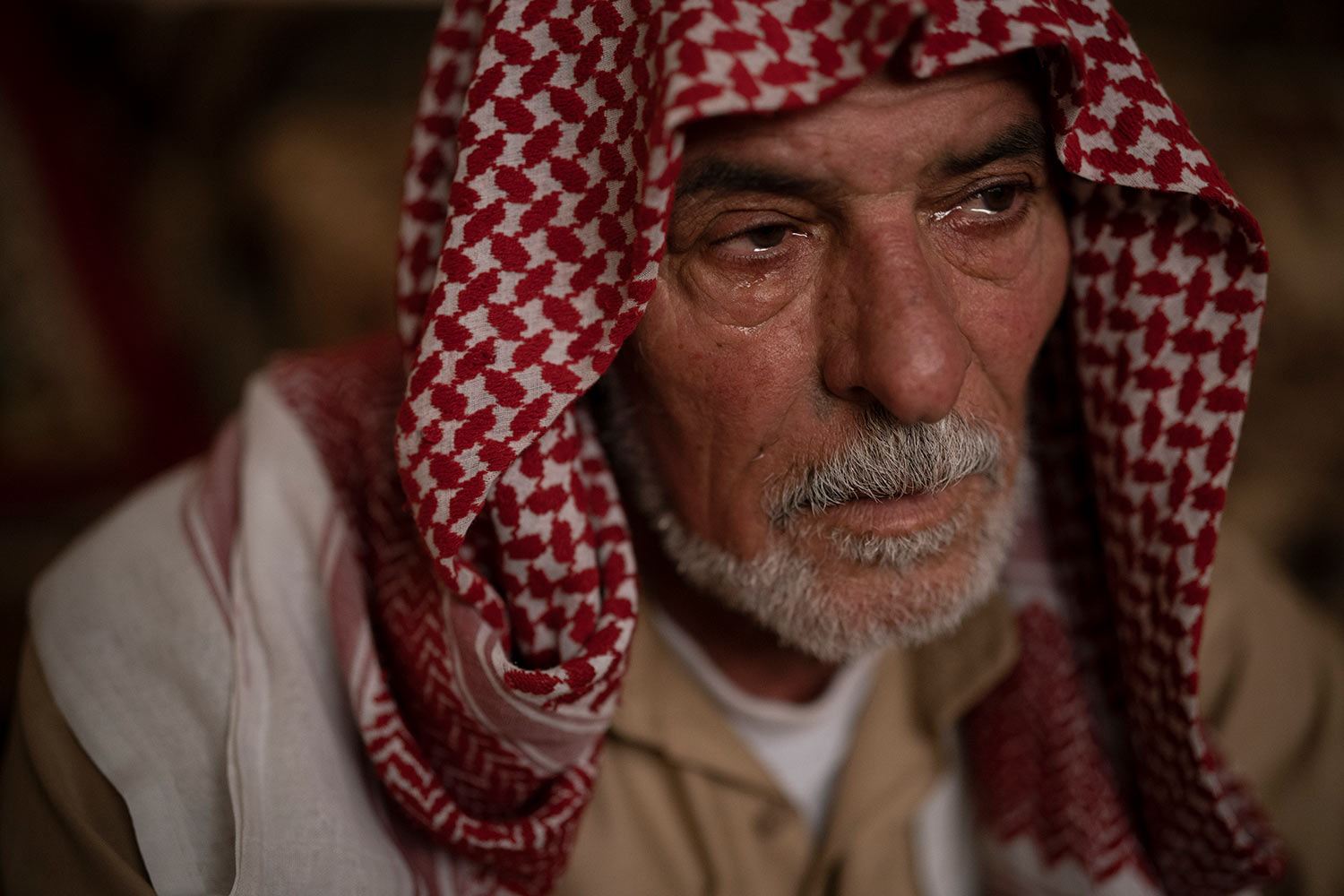 In this April 14, 2019 photo, Hussein Abd cries while talking about the death of his three sons as he sits in his house in Mosul, Iraq. They were killed in Badoush by Islamic State militants in a chilling attack last January. (AP Photo/Felipe Dana)