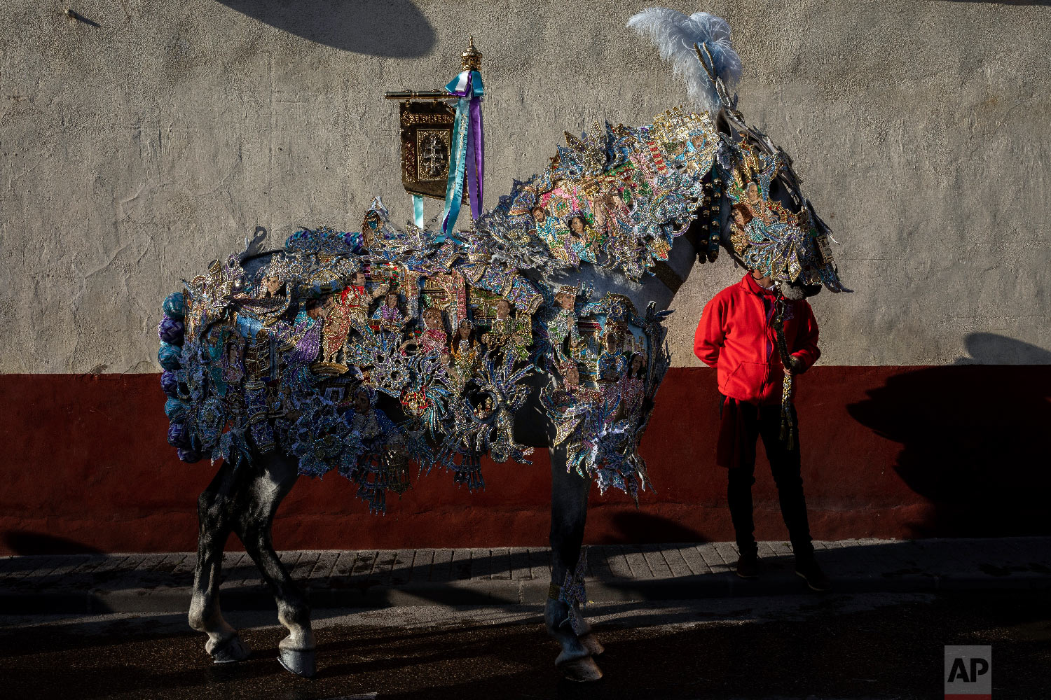 "A horse and entrant of ""Los Caballos del Vino,"" usually translated as the Running of the Wine Horses, wait in downtown for the start of the competition in Caravaca de la Cruz, southeast Spain, Thursday, May 2, 2019. (AP Photo/Bernat Armangue)"