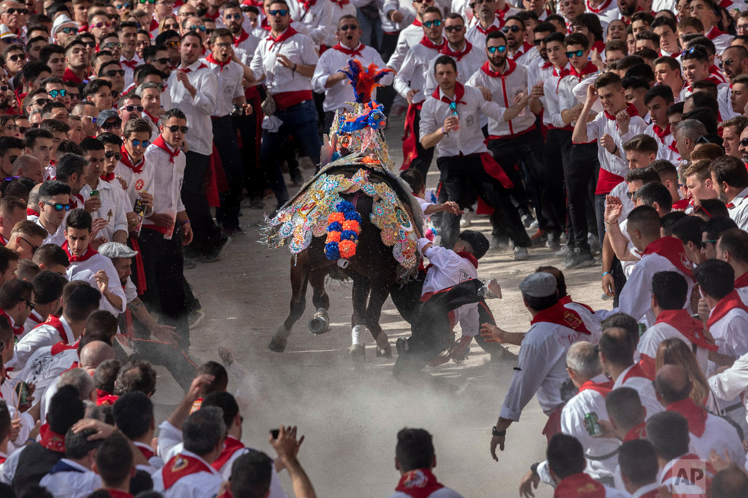 "A troupe falls down while their horse make its way amid the crowd during the ""Los Caballos del Vino,"" usually translated as the Running of the Wine Horses in Caravaca de la Cruz, southeast Spain, Thursday, May 2, 2019. (AP Photo/Bernat Armangue)"