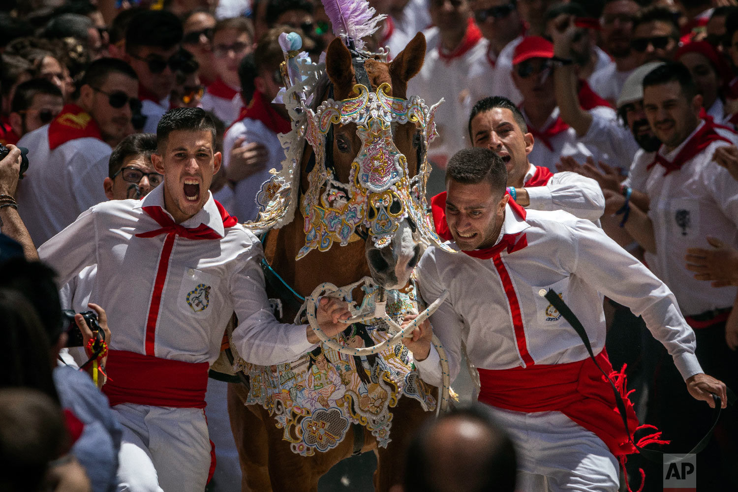 "A troupe and their richly decorated horse make their way amid the crowd during the ""Los Caballos del Vino,"" usually translated as the Running of the Wine Horses in Caravaca de la Cruz, southeast Spain, Thursday, May 2, 2019. (AP Photo/Bernat Armangue)"