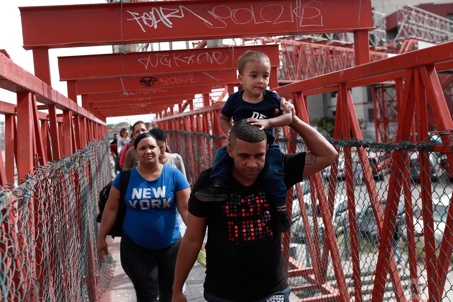 Cuban migrants are escorted by Mexican immigration officials as they cross the Paso del Norte International bridge to be processed as asylum seekers on the U.S. side of the border. (AP Photo/Christian Torres)