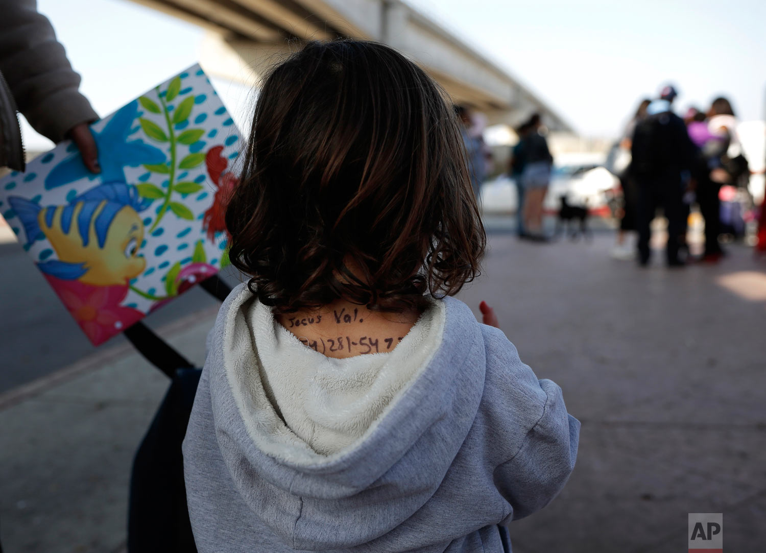 The back of a girl from the Mexican state of Michoacan displays a name and number, written in ink. She waits to apply for asylum in the United States with her mom and sister, in Tijuana, Mexico, April 25, 2019. Her mother said she wrote the information on her daughter because she feared losing track of the child if separated during the asylum application process. (AP Photo/Gregory Bull)