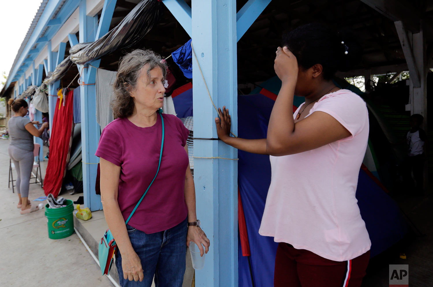 Jennifer Harbury, left, a human rights lawyer, speaks to an asylum seeker in Reynosa, Mexico, May 1, 2019. (AP Photo/Eric Gay)